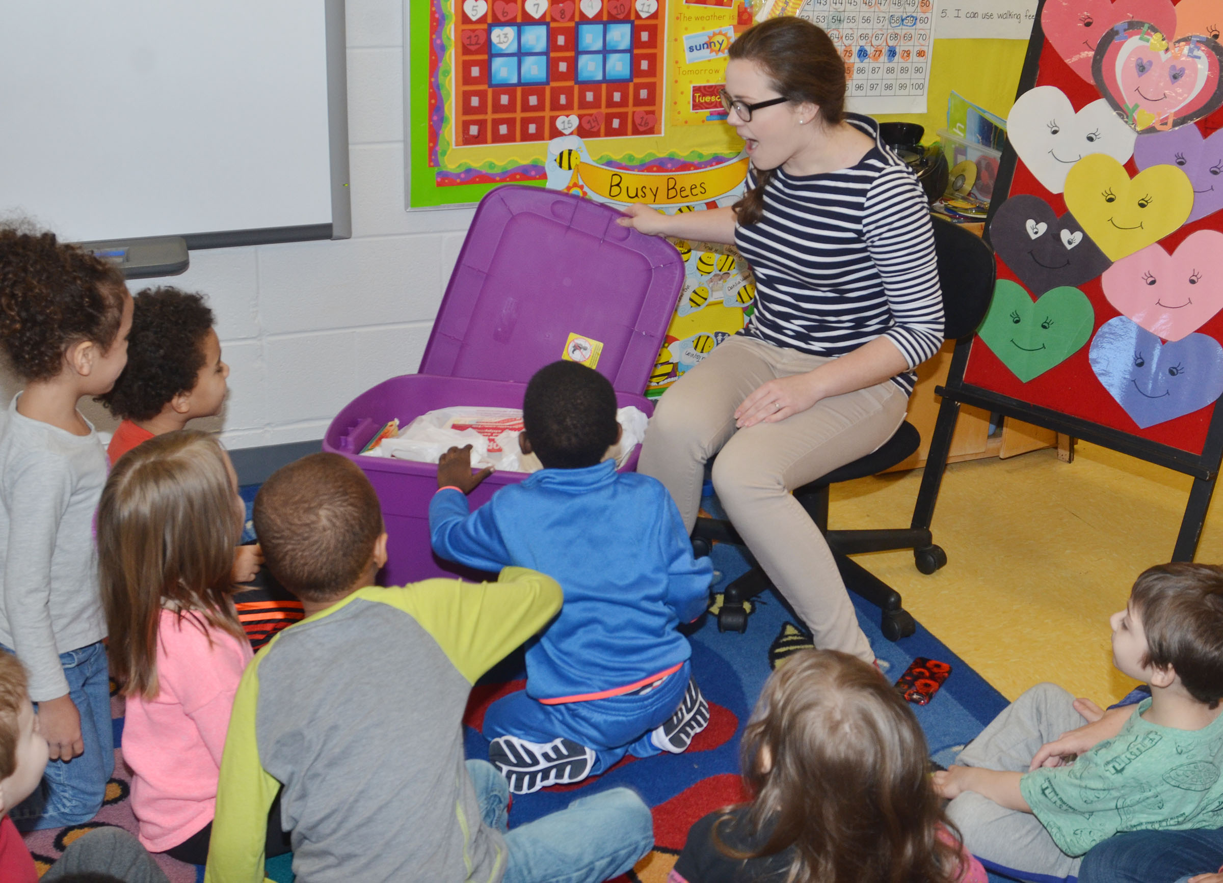 Campbellsville University education student Amanda Hamilton shows CES preschool students the books that were donated to them.