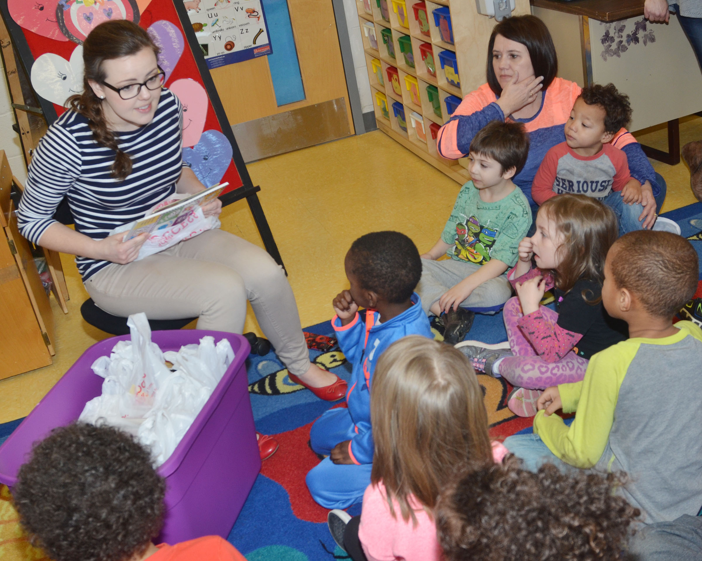 Campbellsville University education student Amanda Hamilton passes out donated books to CES preschool students.