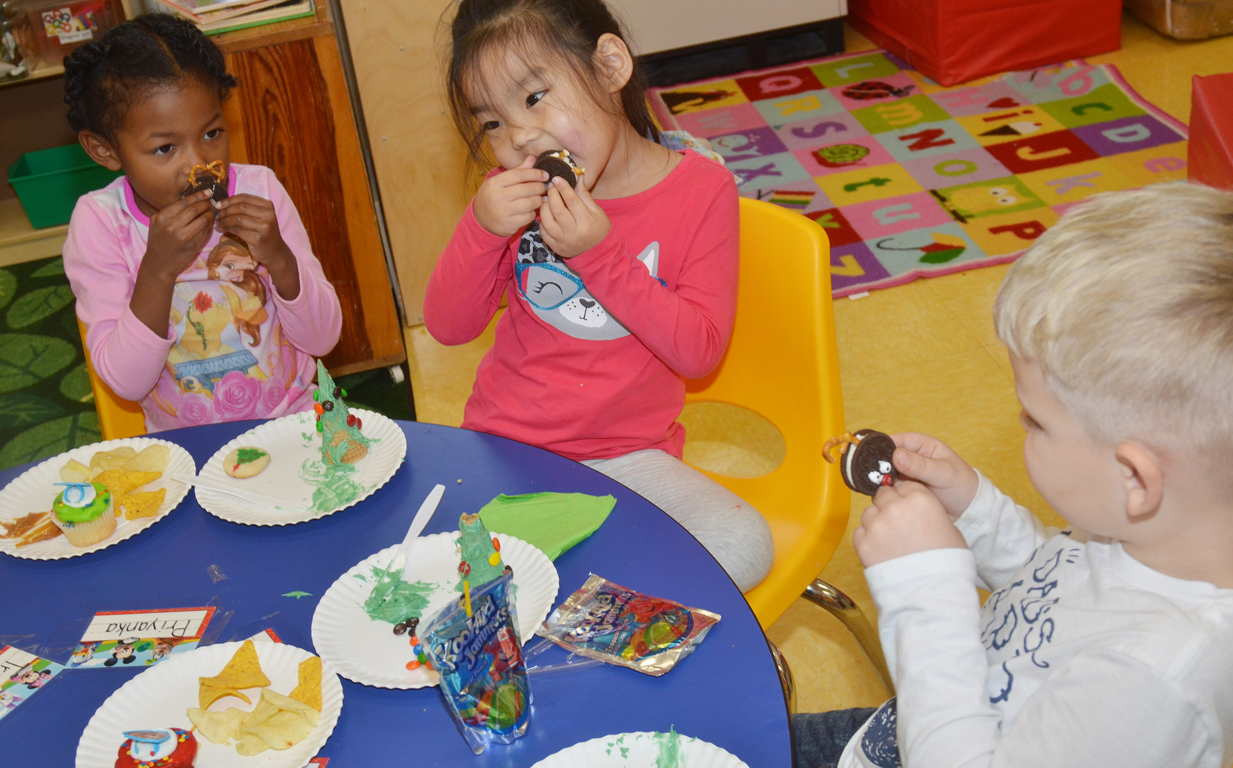 From left, CES preschool students Priyanka Flores, Marla Bat and Hoyt Davis enjoy their class Christmas party.
