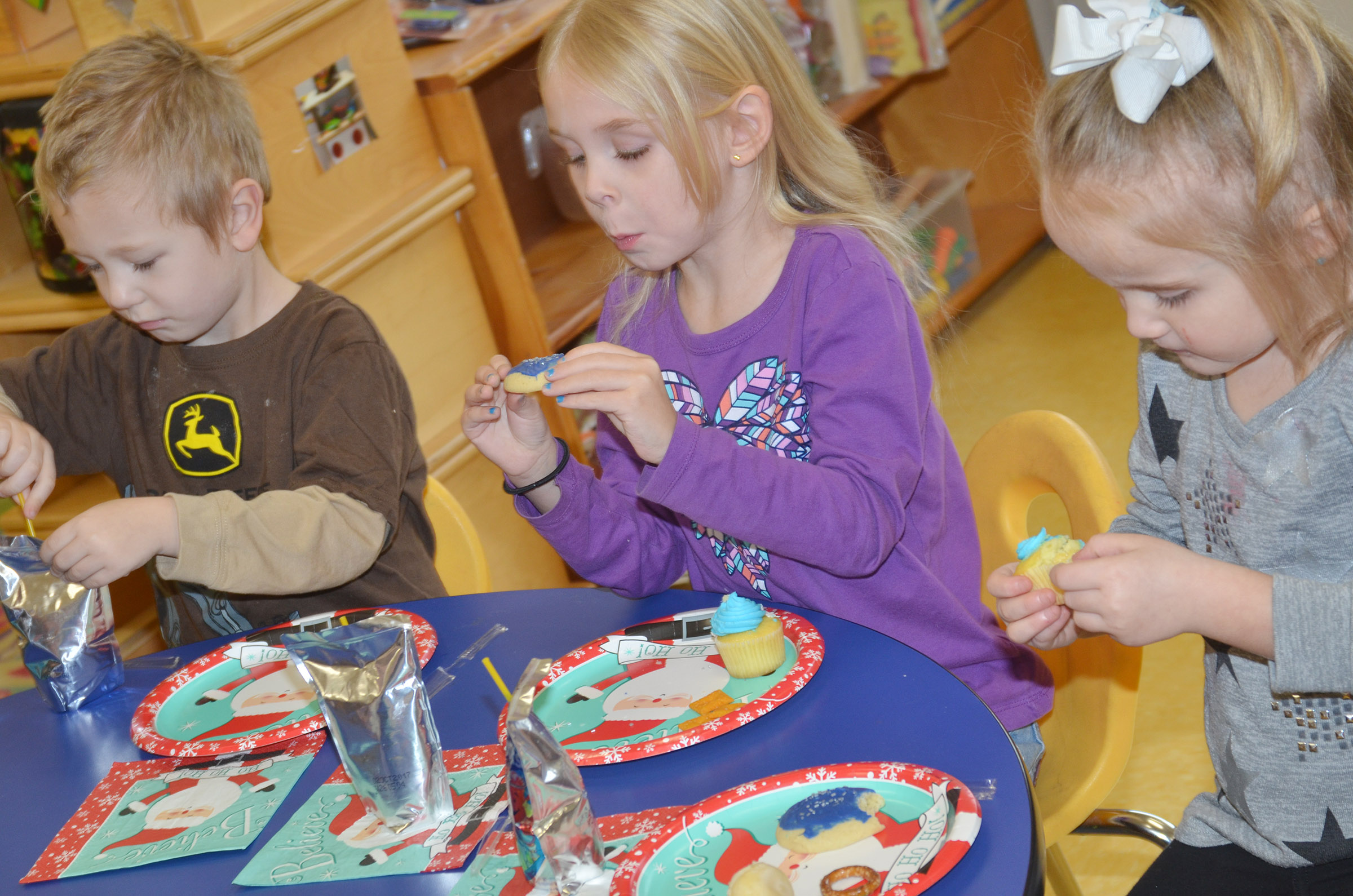 From left, CES preschool students Cameron Dean, Alinna Bray and Trinity Dye enjoy their snacks.