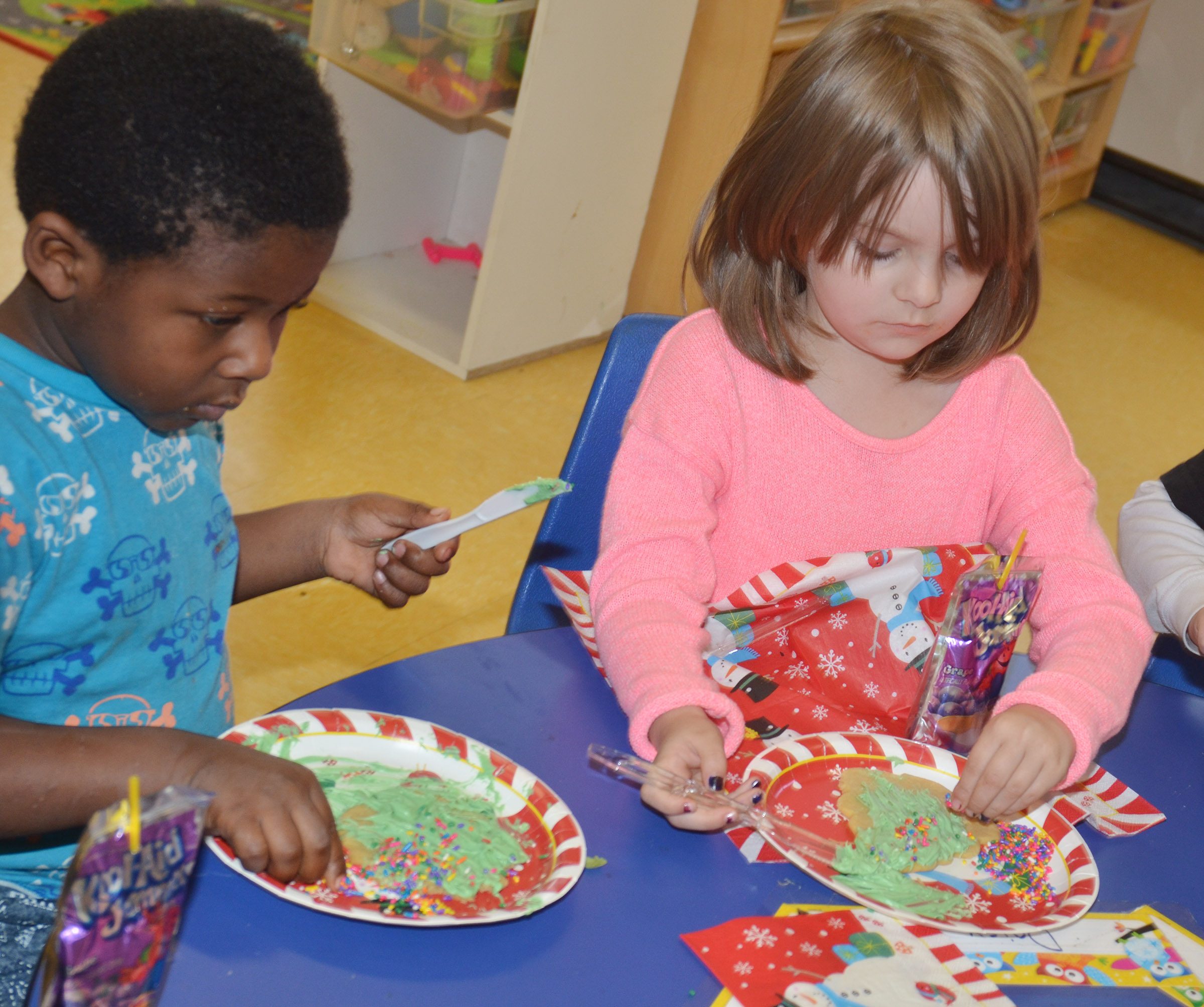CES preschool students LaTayvion Brown, at left, and Daisy Rakes decorate their cookies.