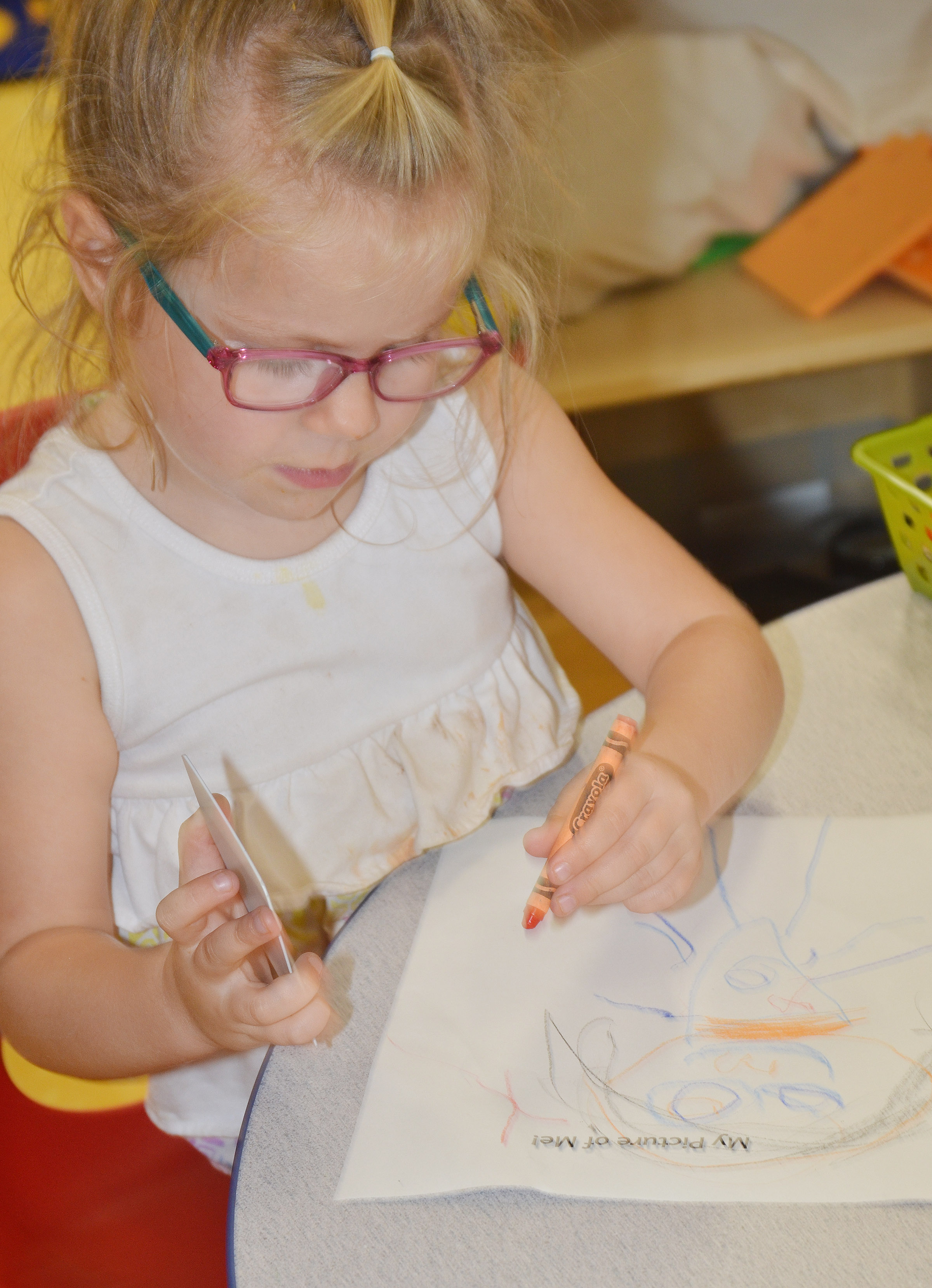 CES preschool student Charlotte Coots draws a self-portrait.