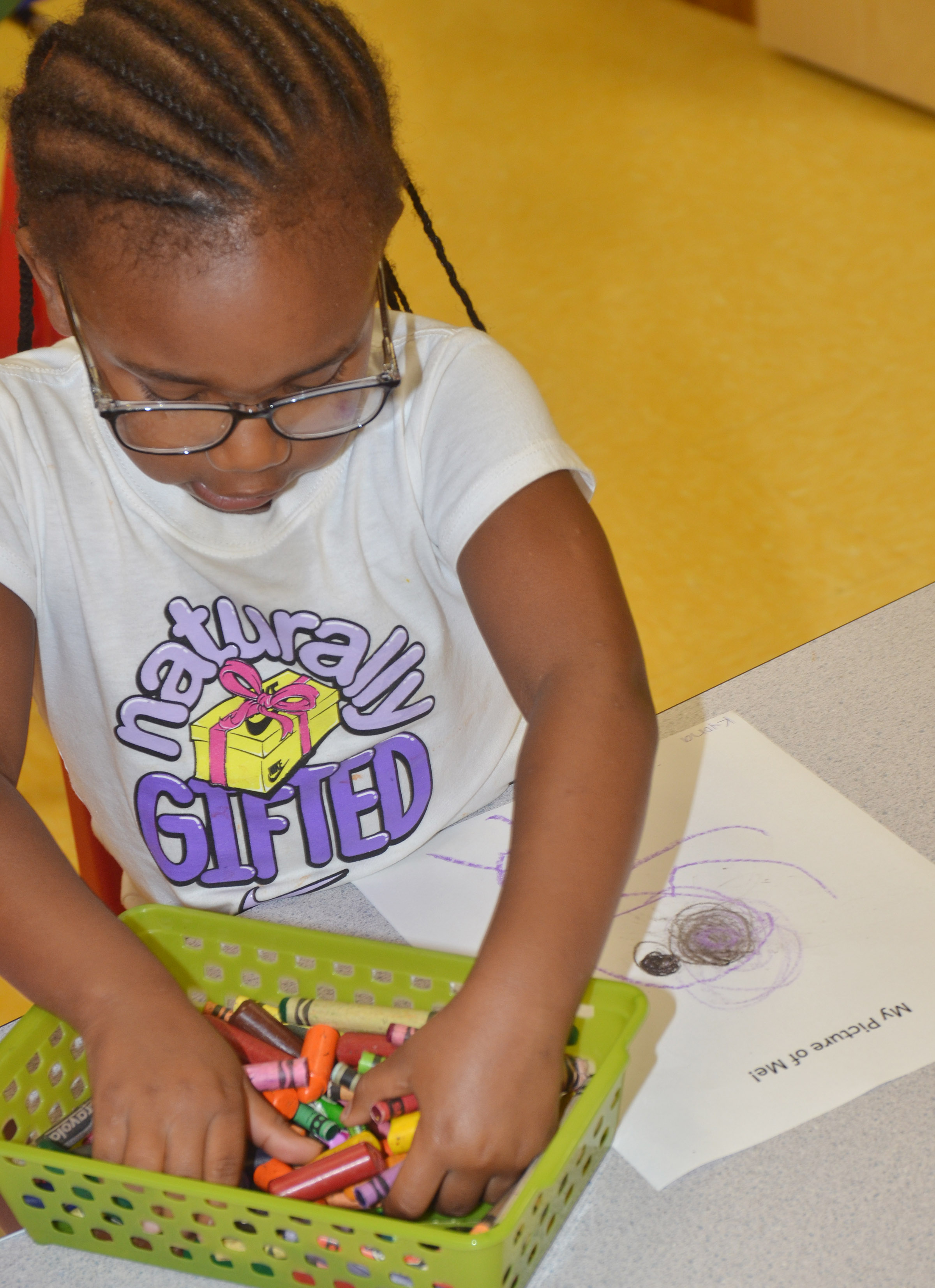 CES preschool student Kyona Mitchell draws a self-portrait.