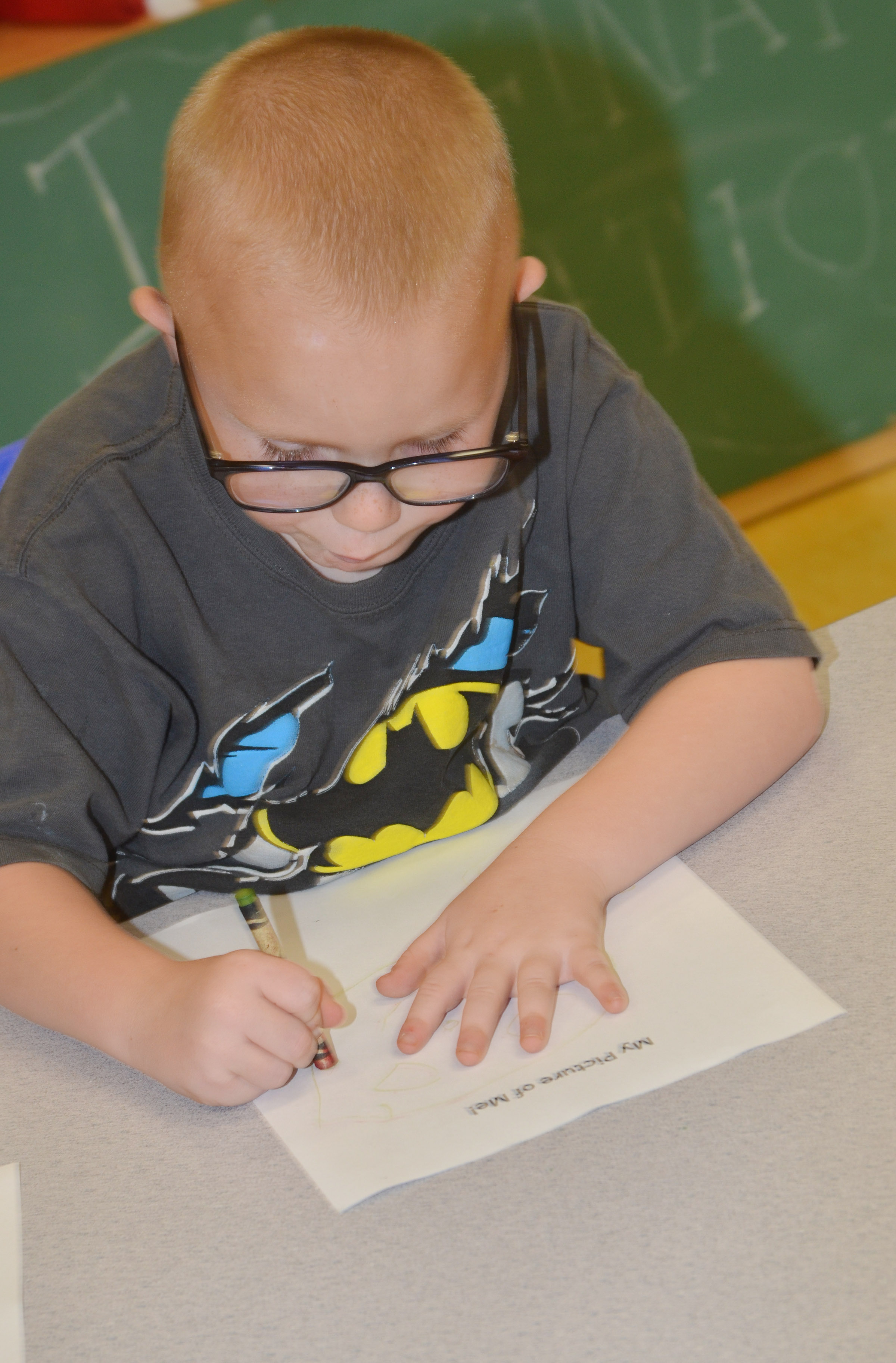 CES preschool student Anthony McClure draws a self-portrait.