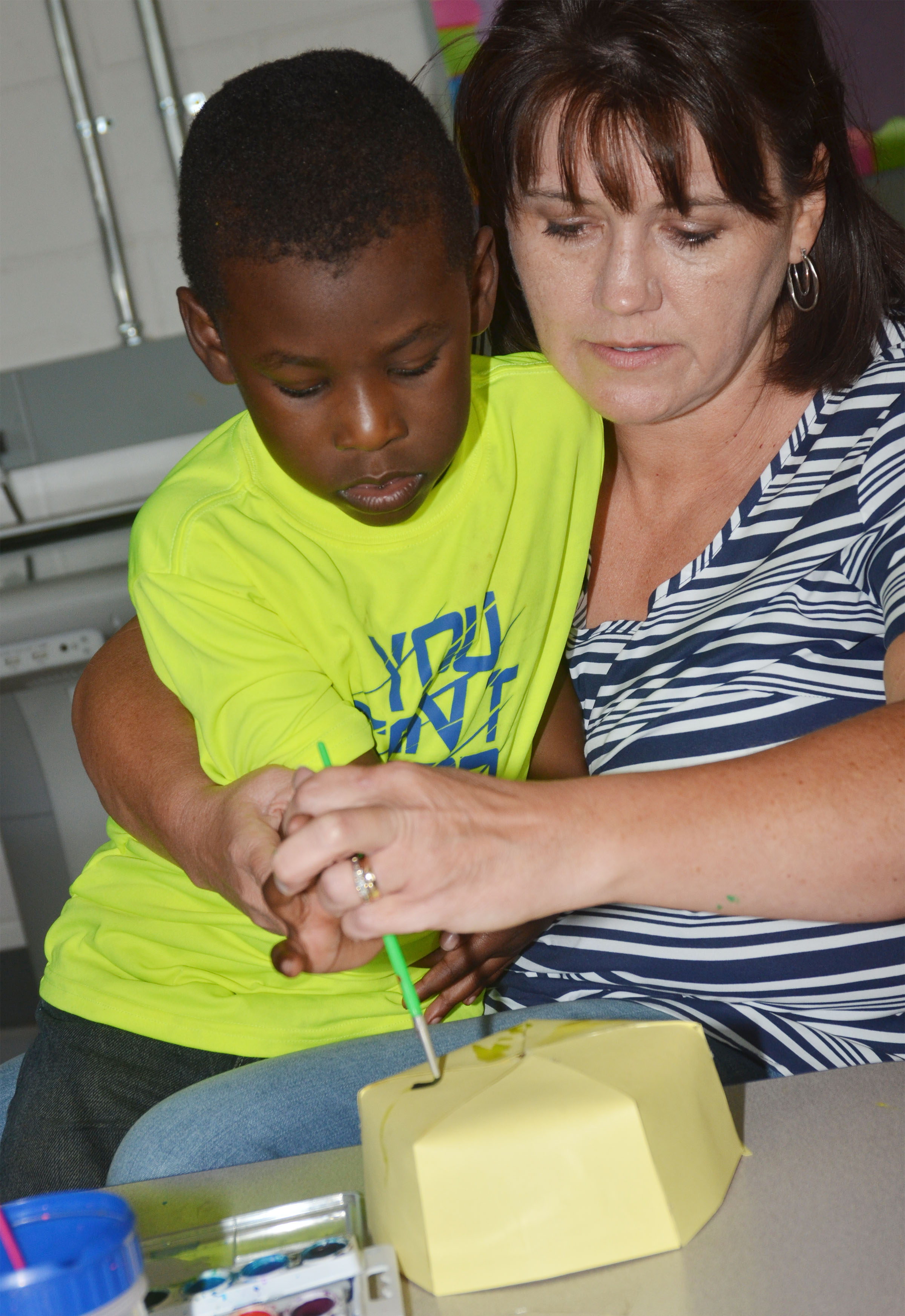 CES preschool student Trezdyn Tonge paints with teacher Denise Cowherd.