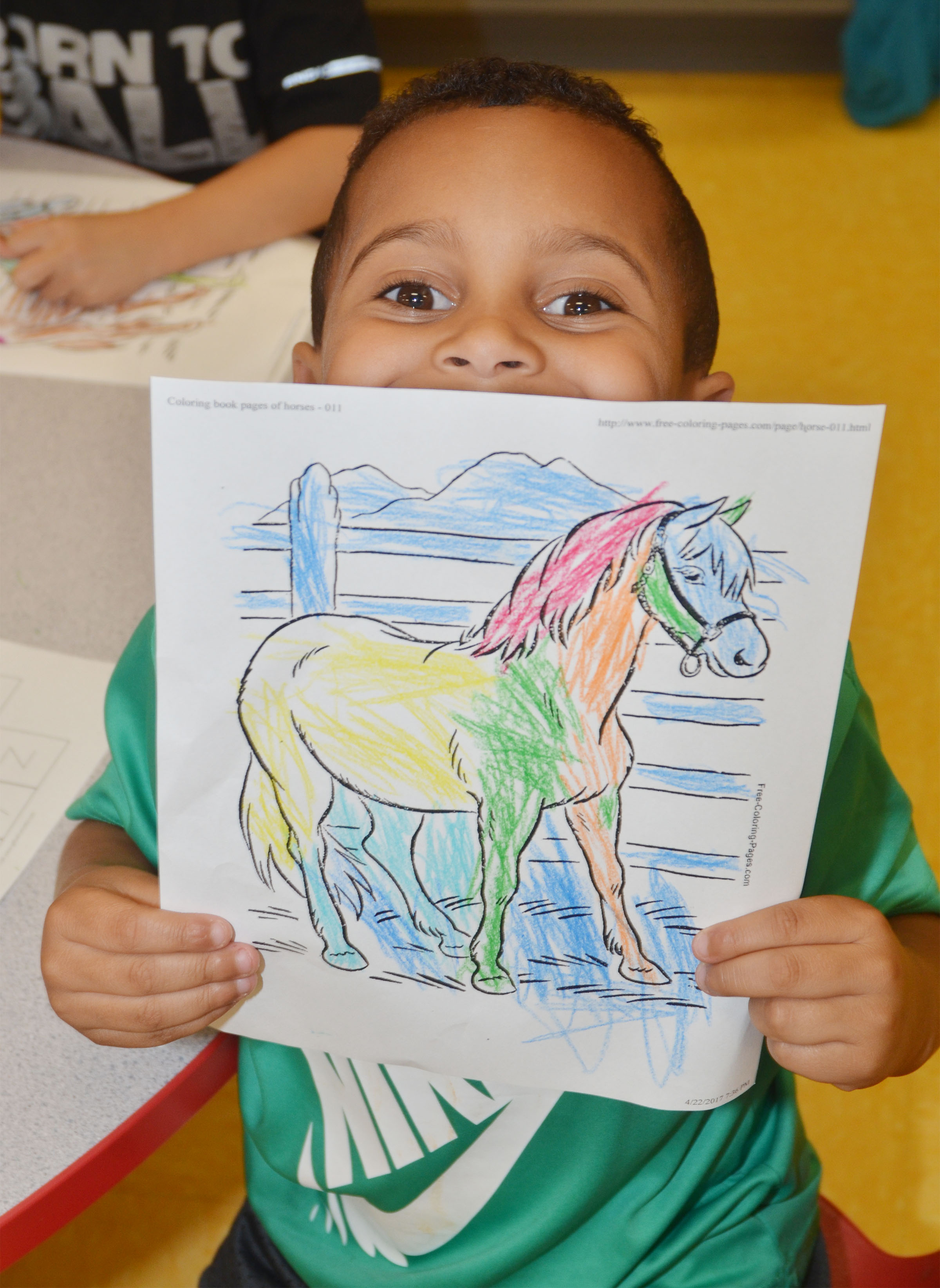 CES preschool student Kingston Cowherd holds a horse picture she colored.
