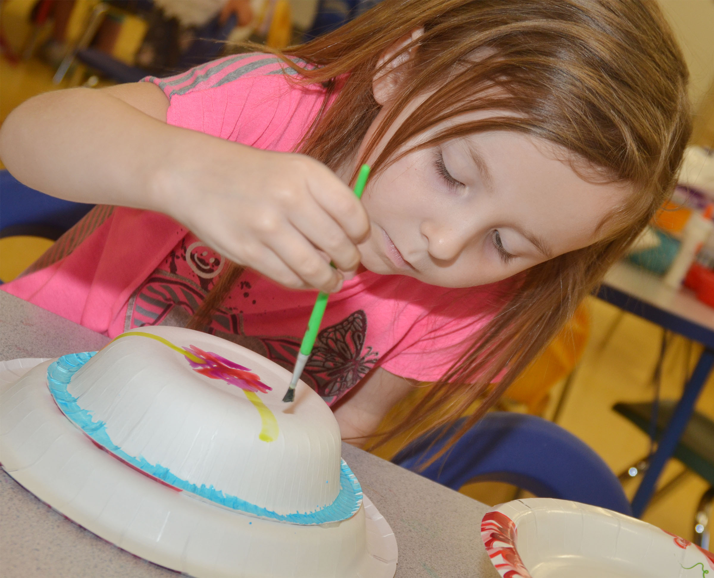 CES preschool student Tabitha Leggett paints her Derby hat.