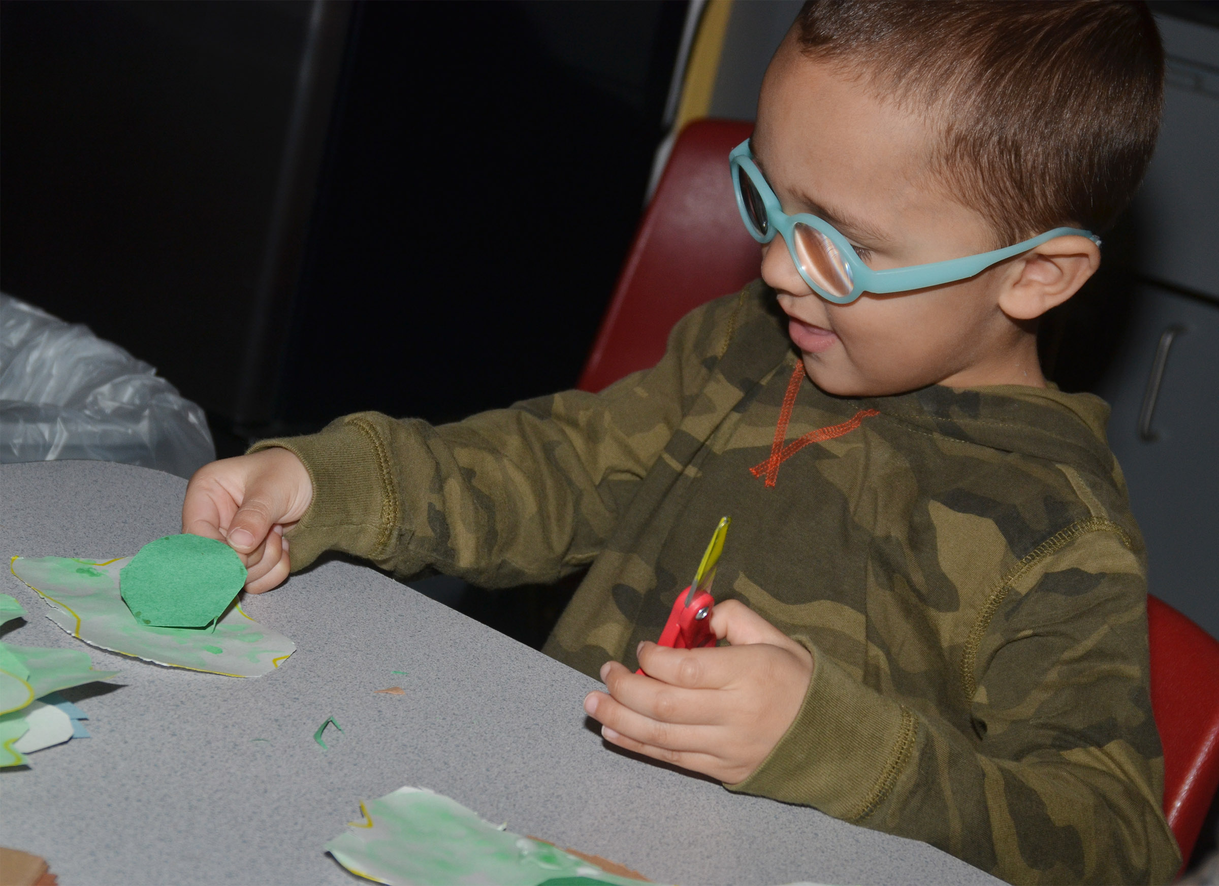 "CES preschool student Chanler Mann cuts out his egg for his ""Green Eggs and Ham"" project."