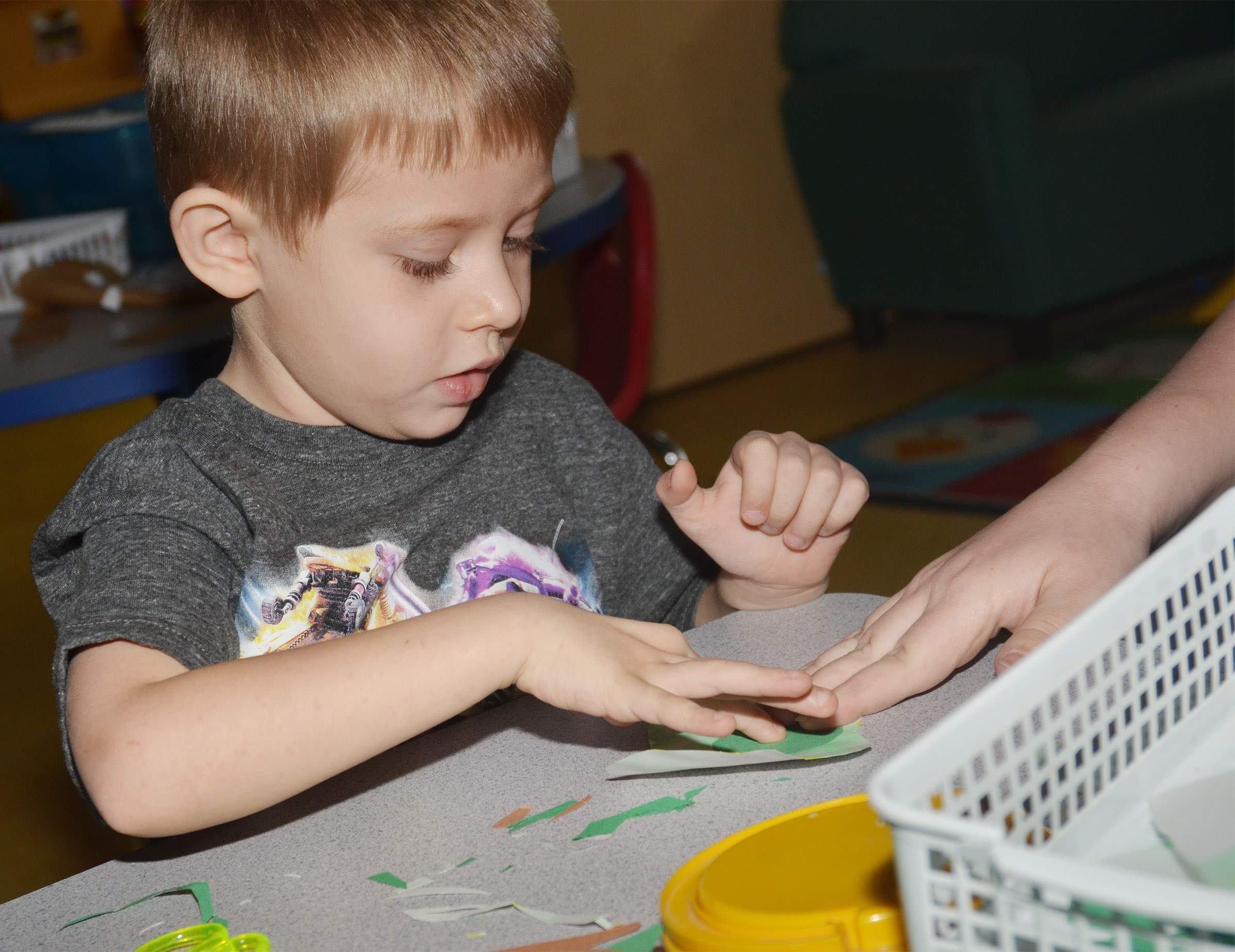 "CES preschool student Elijah Russell glues his egg for his ""Green Eggs and Ham"" project."