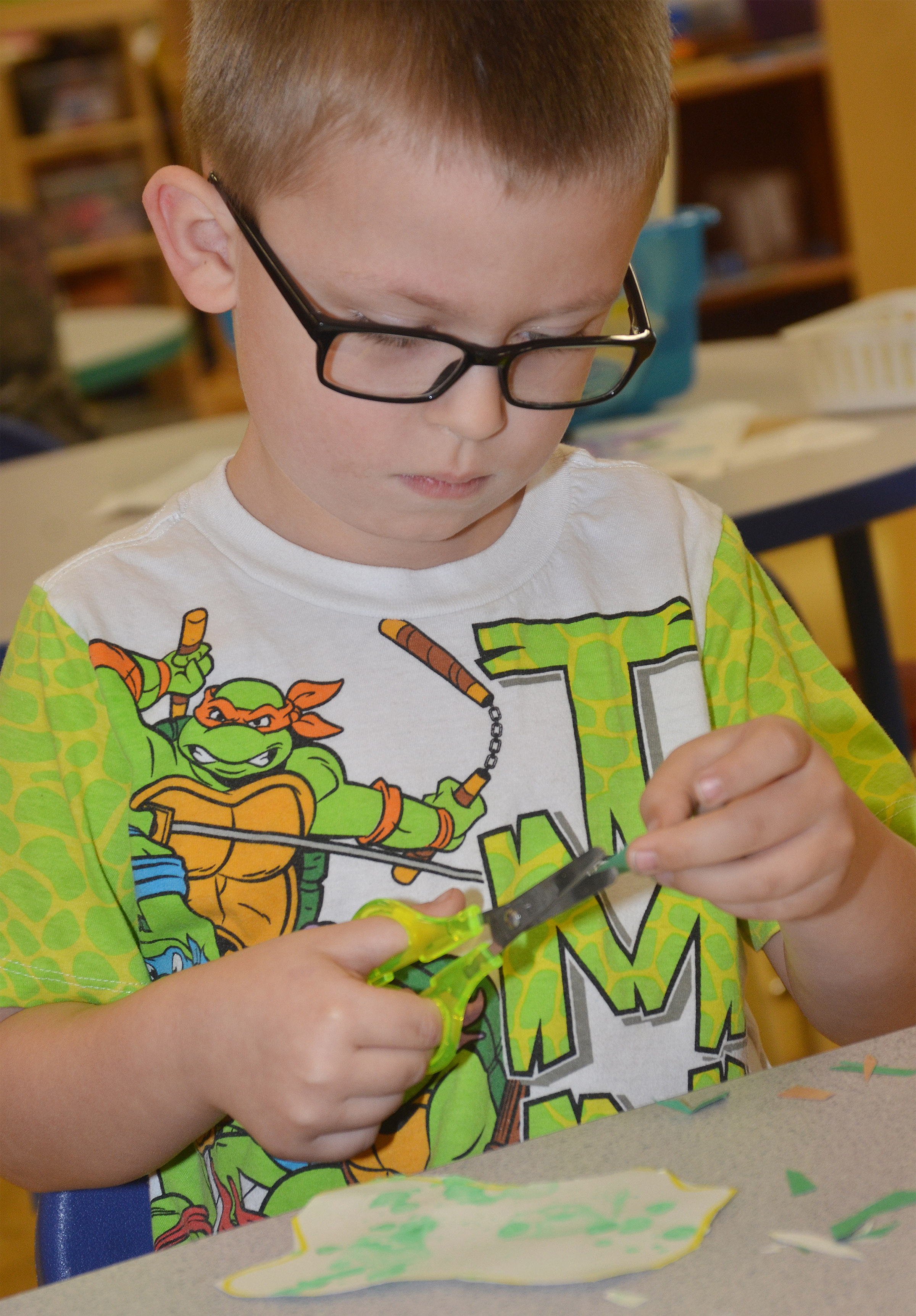 "CES preschool student Reece Williams cuts out his egg for his ""Green Eggs and Ham"" project."