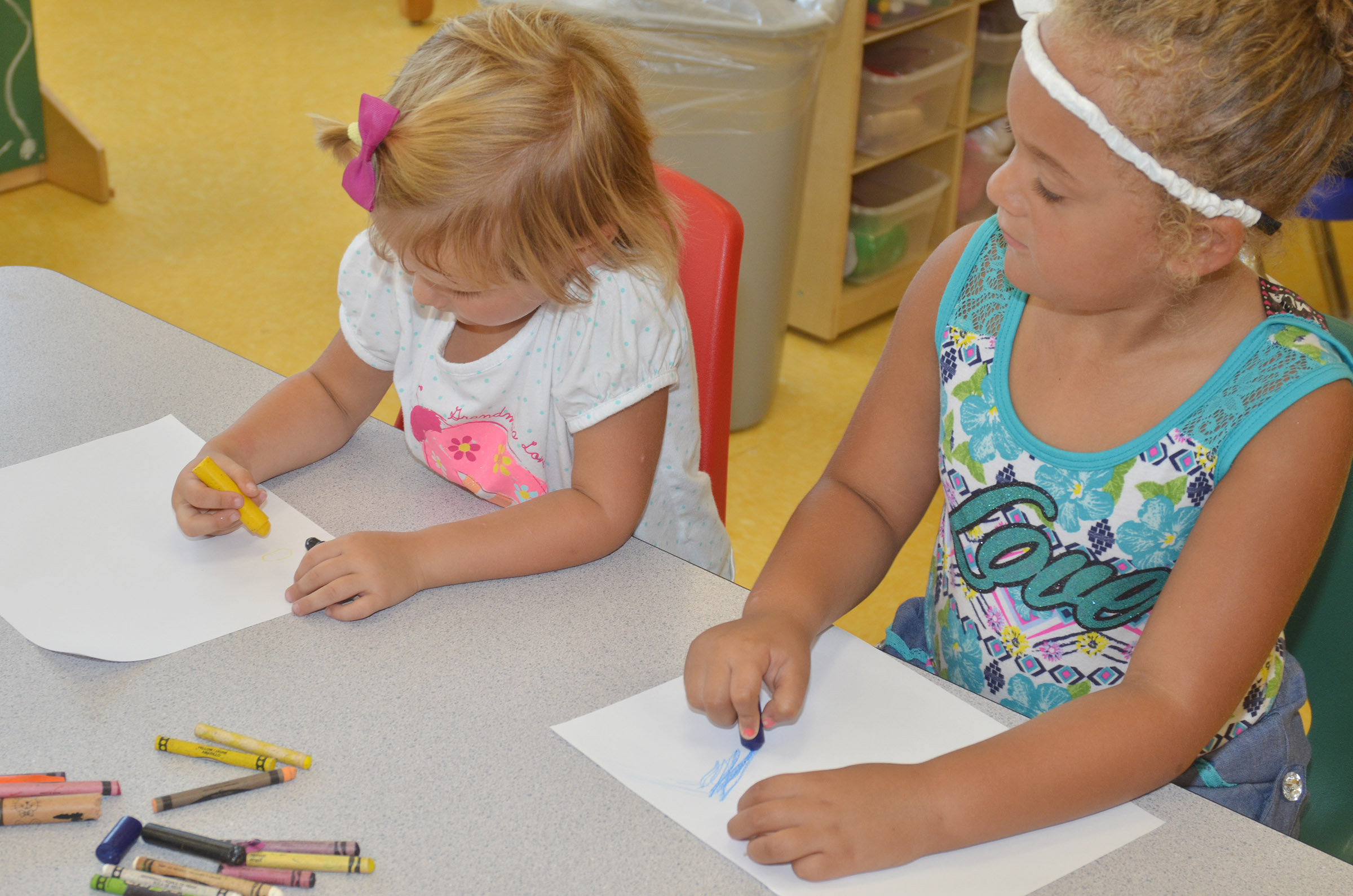 CES preschool students Elliana Morton, at left, and Layla Barbee color pictures of their houses.