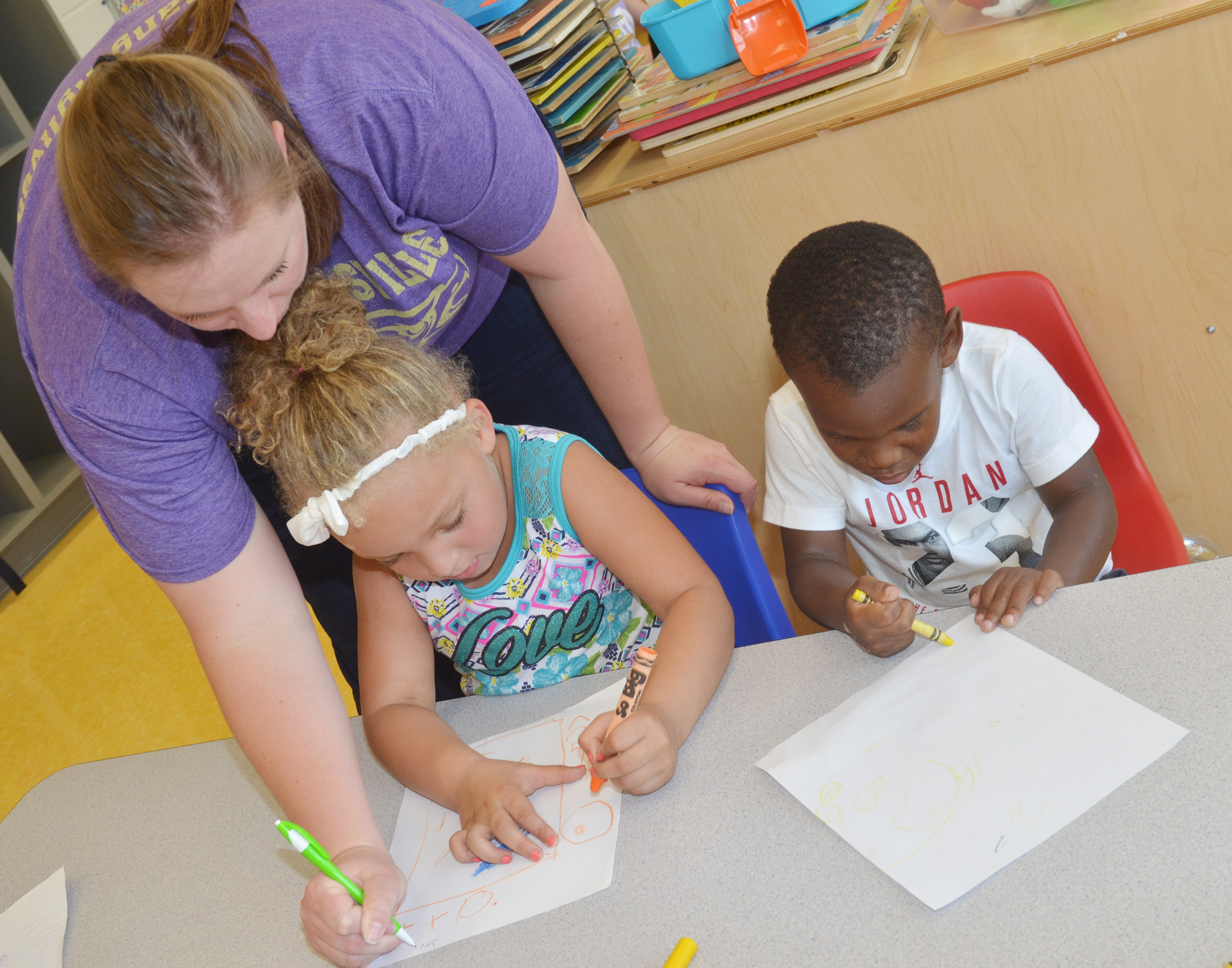 CES preschool students Jayla Barbee, at left, and Mason Conner color a picture of their houses, as teacher Julie Shelton writes their names on their papers.