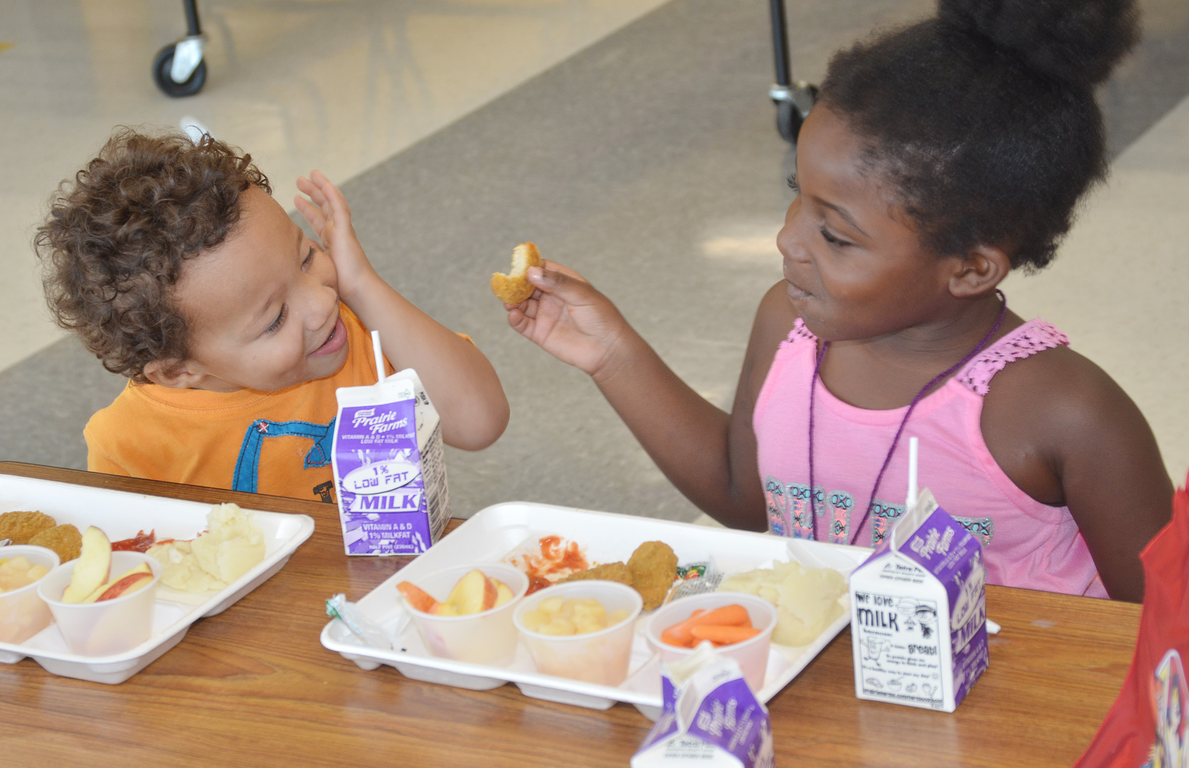 CES preschool students Ace Turner, at left, and Harmony Brown talk as they eat lunch together.