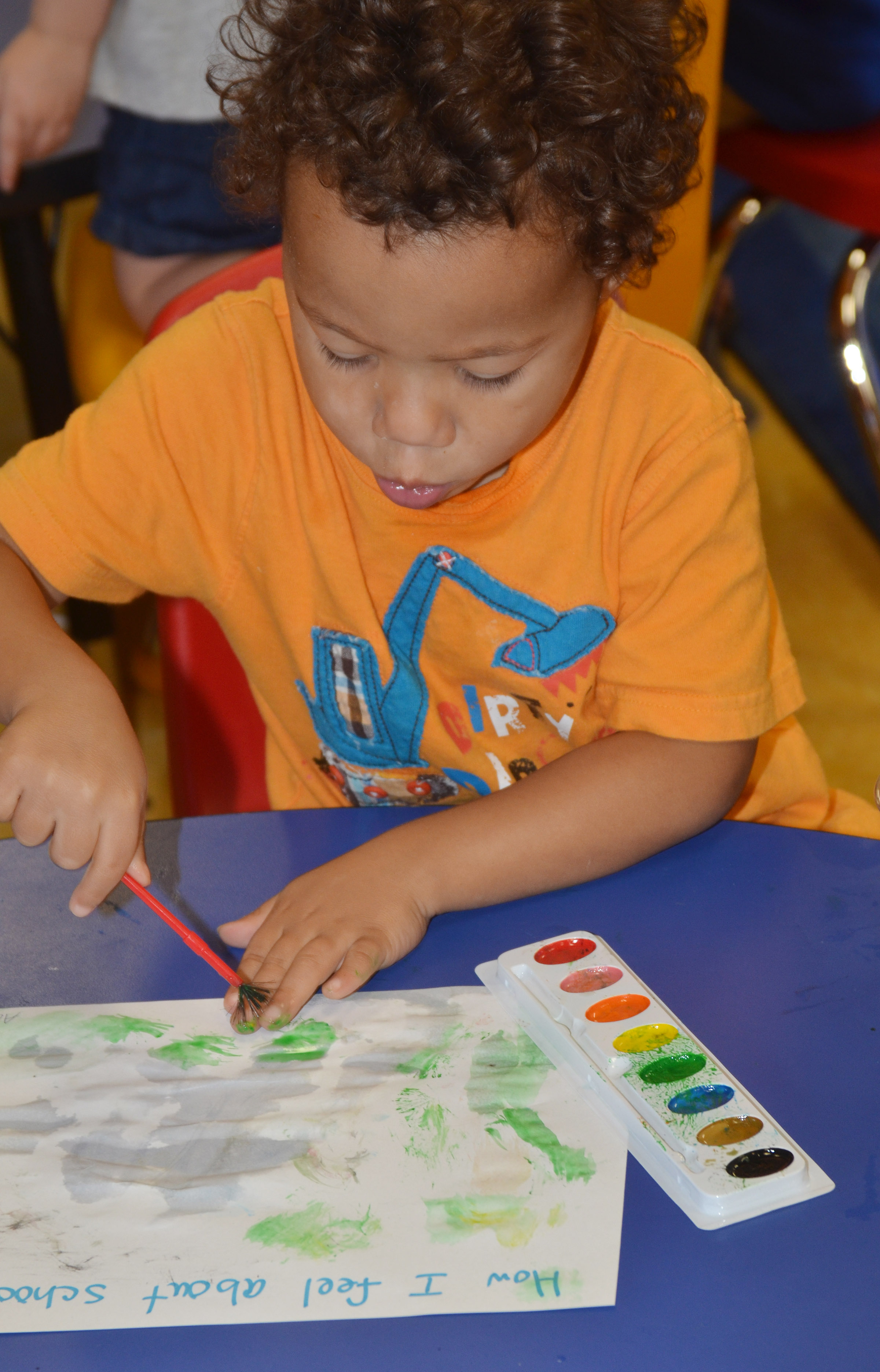 CES preschool student Ace Turner paints how he feels about school.