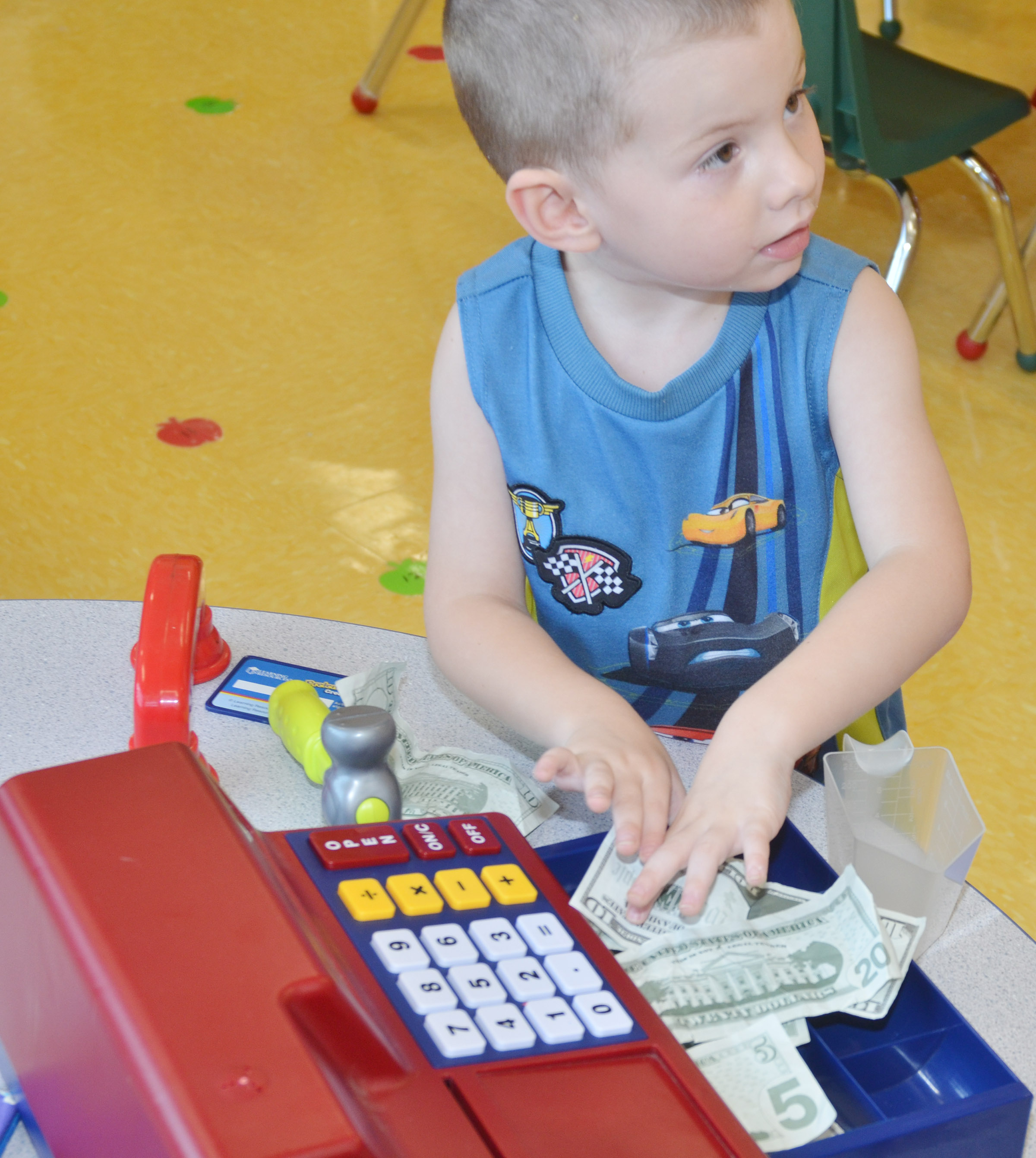 CES preschool student Chase Arnett plays with a cash register.