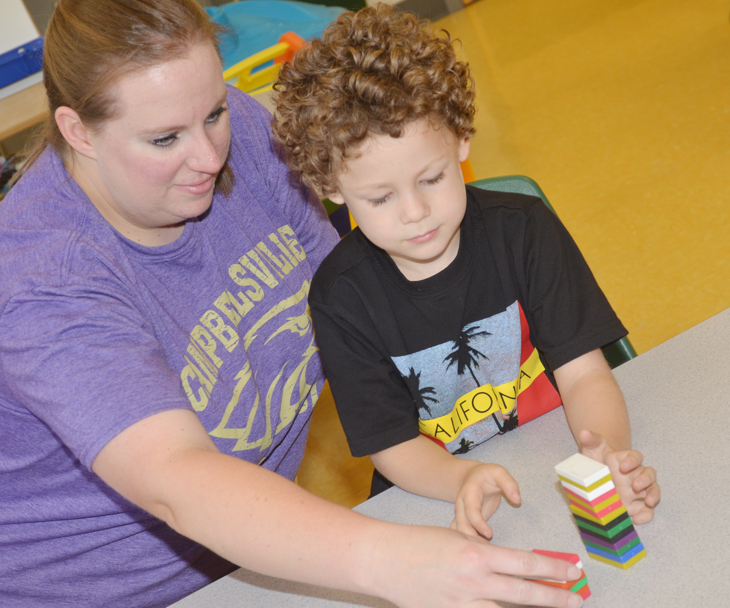 CES preschool teacher Julie Shelton shows student Zyron Young how magnets work.