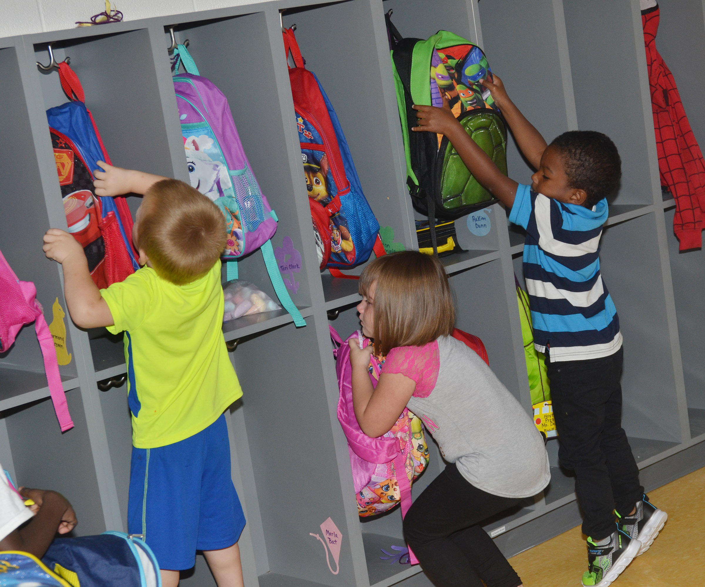 CES preschool students, from left, Landon Allen, Lirra Berry and Rakim Dunn get their backpacks as they prepare to go home after their first day of school.