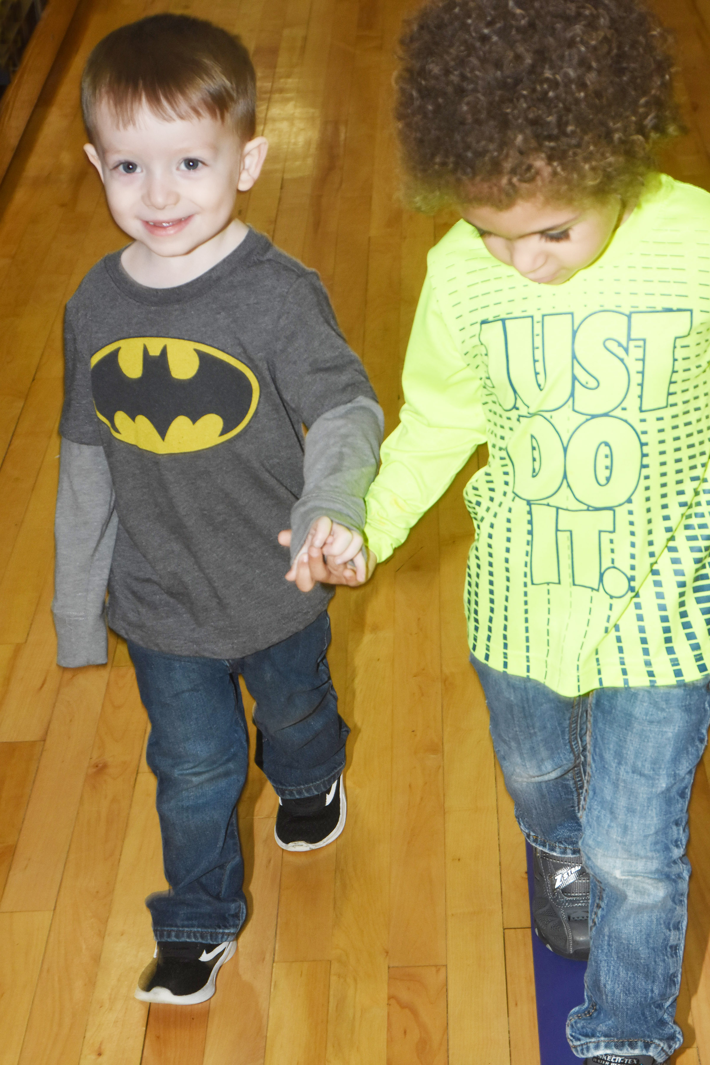 CES preschool students Maddox Creason, at left, and Terren Lasley walk together around the gym.