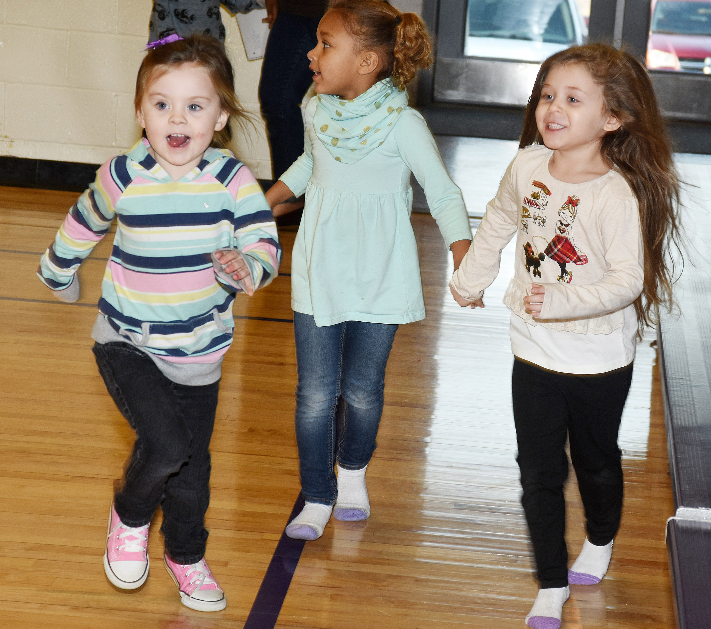 From left, CES preschool students Tori Clark, Adaia Taylor and Mila Moss run in the gym.