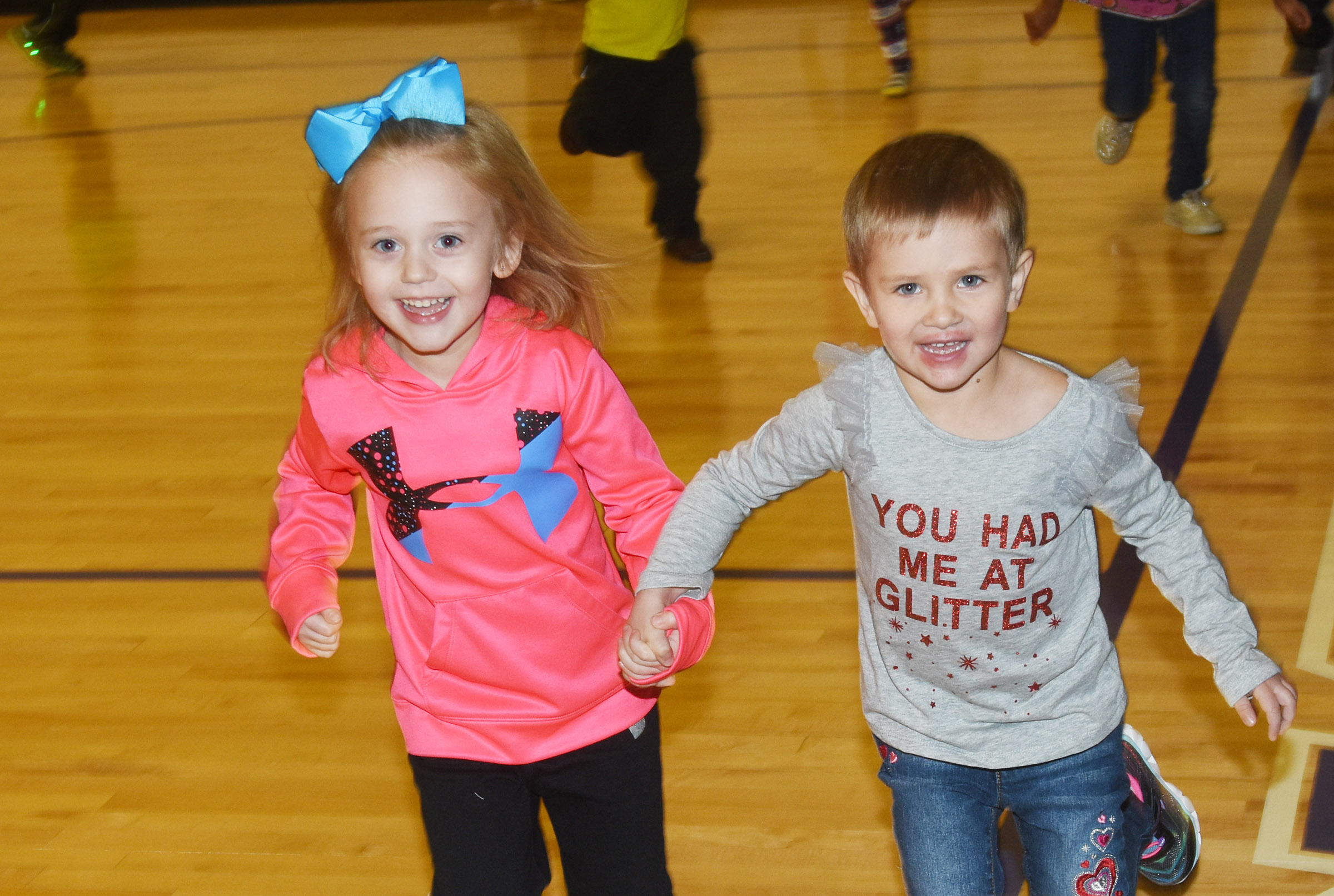CES preschool students Kylie Thompson, at left, and Elliana Morton run together in the gym.