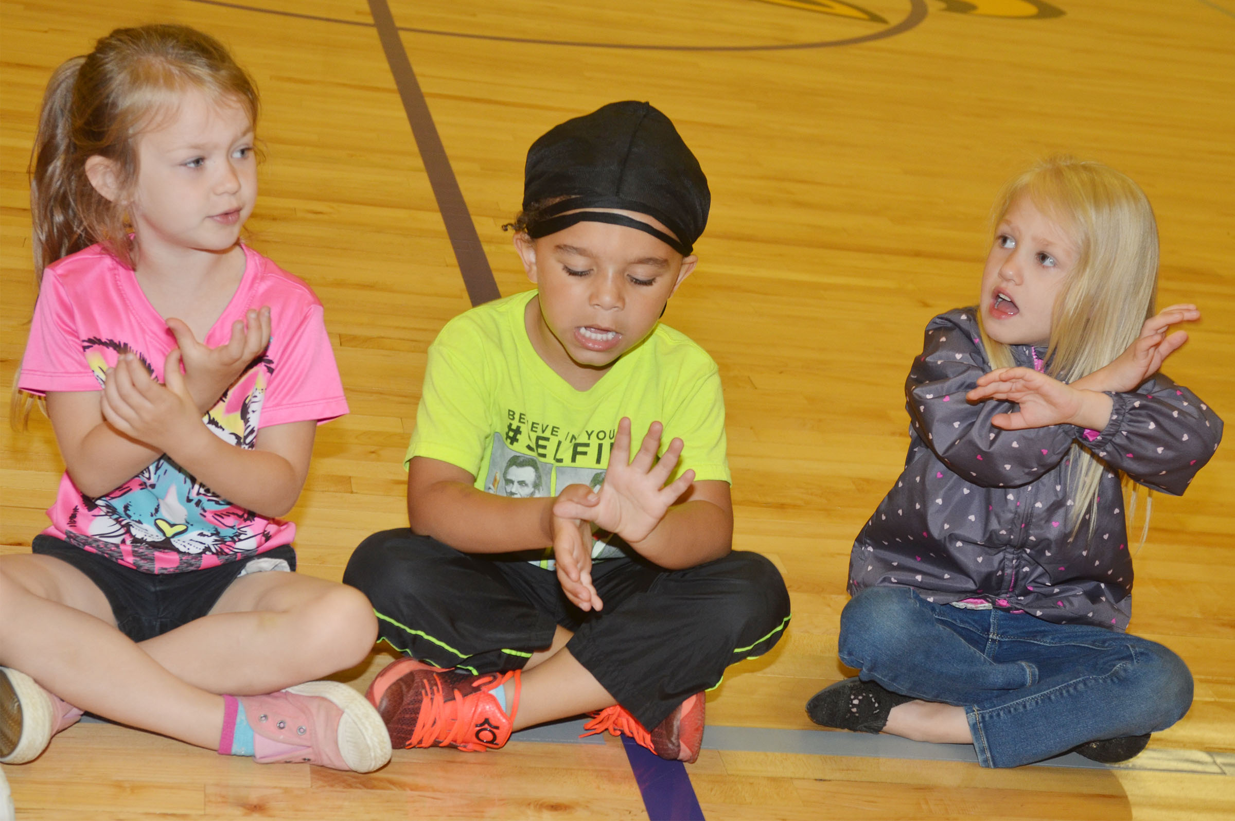 From left, CES preschool students Lilly Spencer Tyrek Moore and Trinity Lewis sing together.