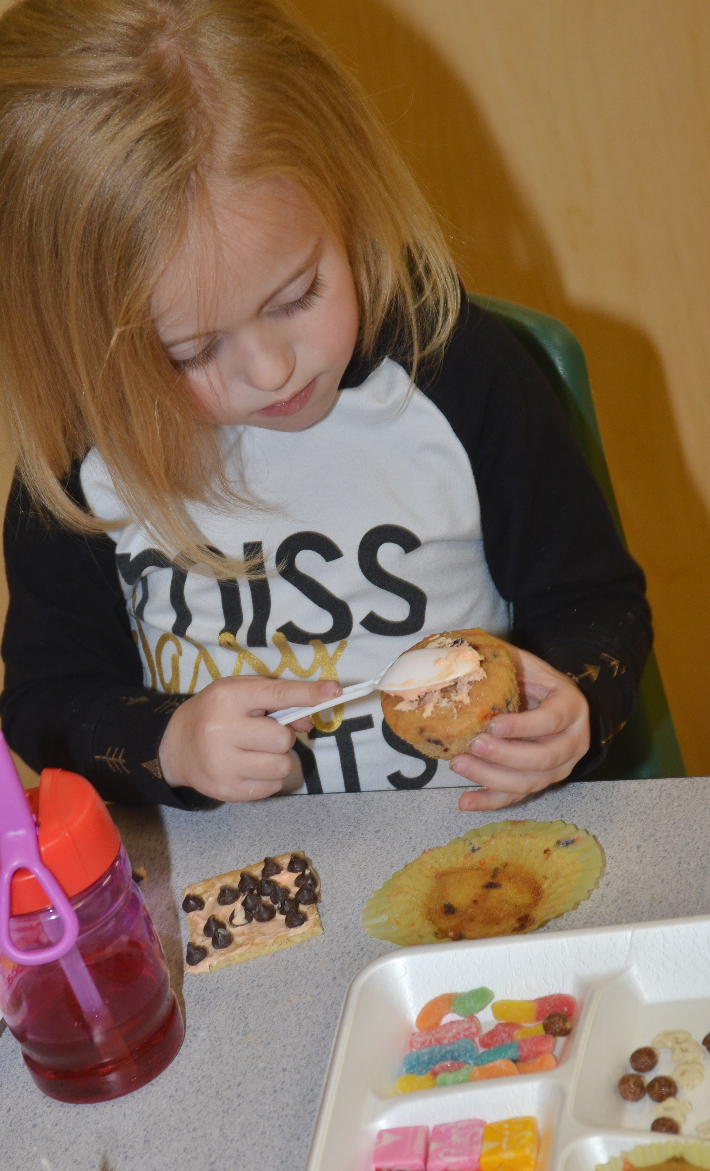 CES preschool student Kylie Thompson adds icing to her cupcake.