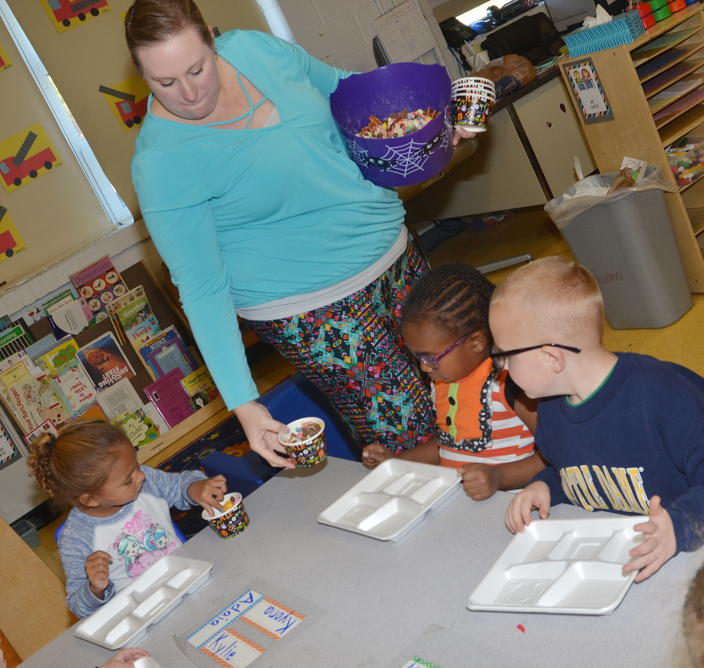 CES preschool teacher Julie Shelton serves her students a cup of their candy mix.