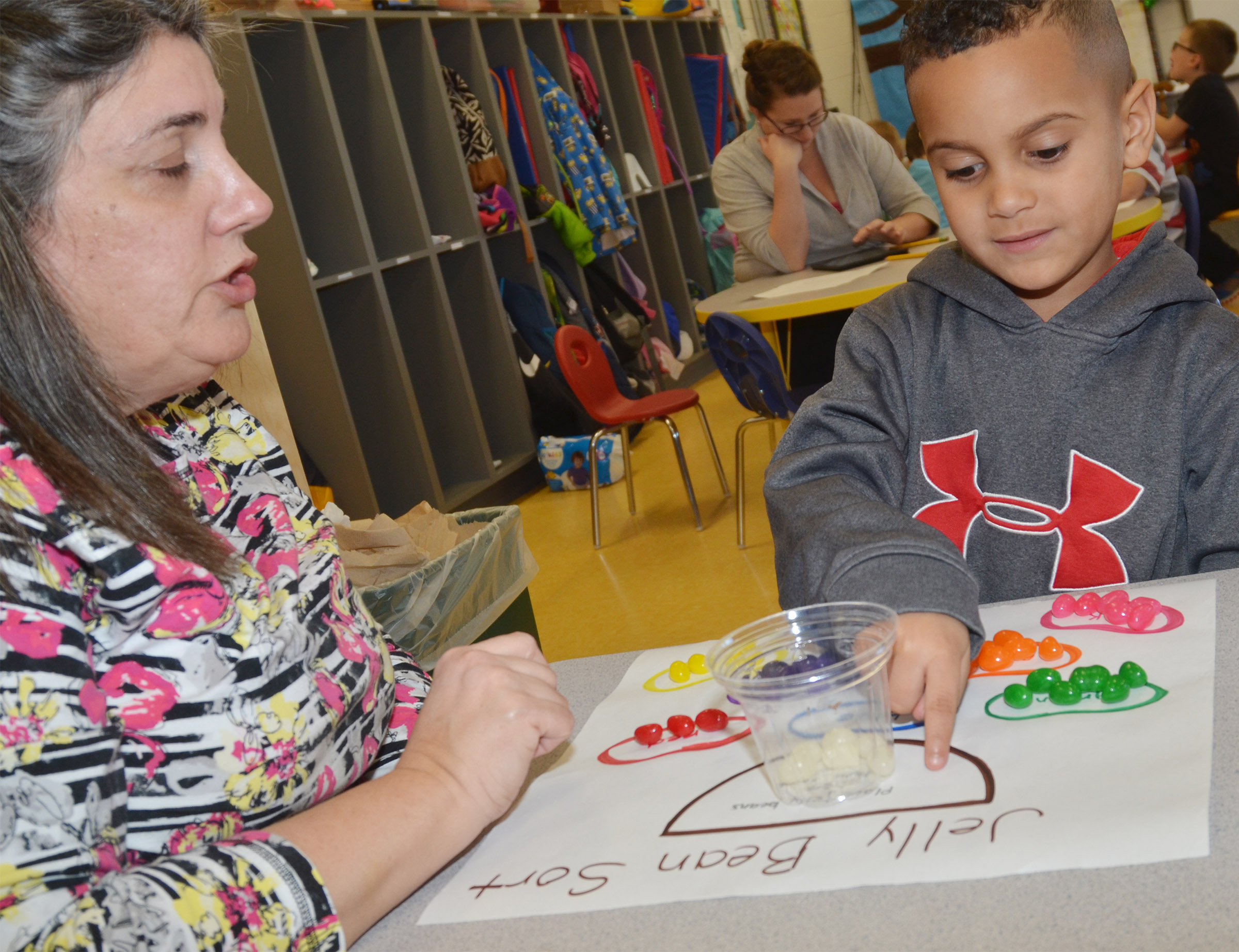 CES preschool student Kingston Cowherd explains to teacher Sherry Cowherd how he sorted his jellybeans.