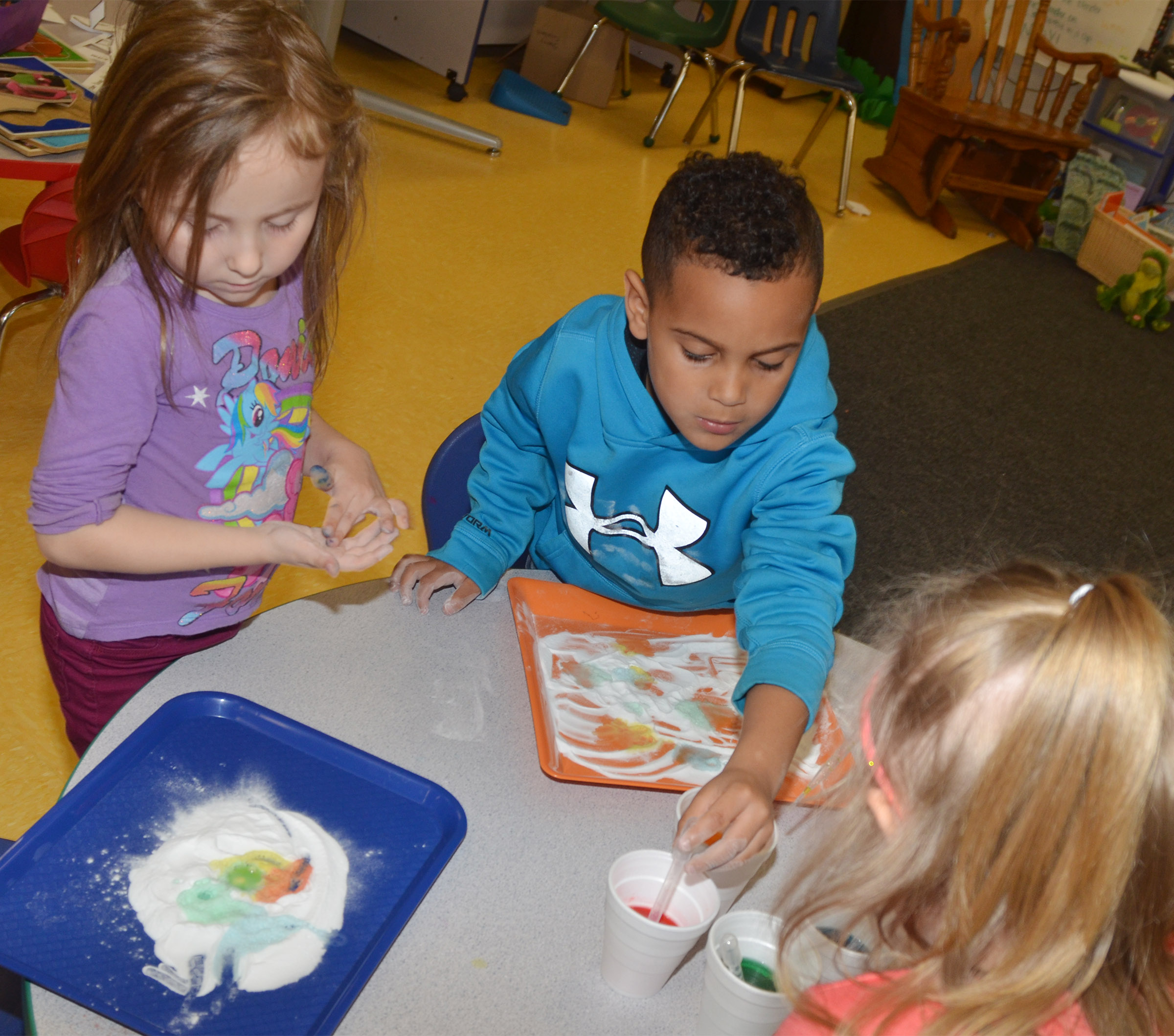 CES preschool students Heather Leggett, at left, and Kingston Cowherd add colored vinegar to baking soda to see its reaction.