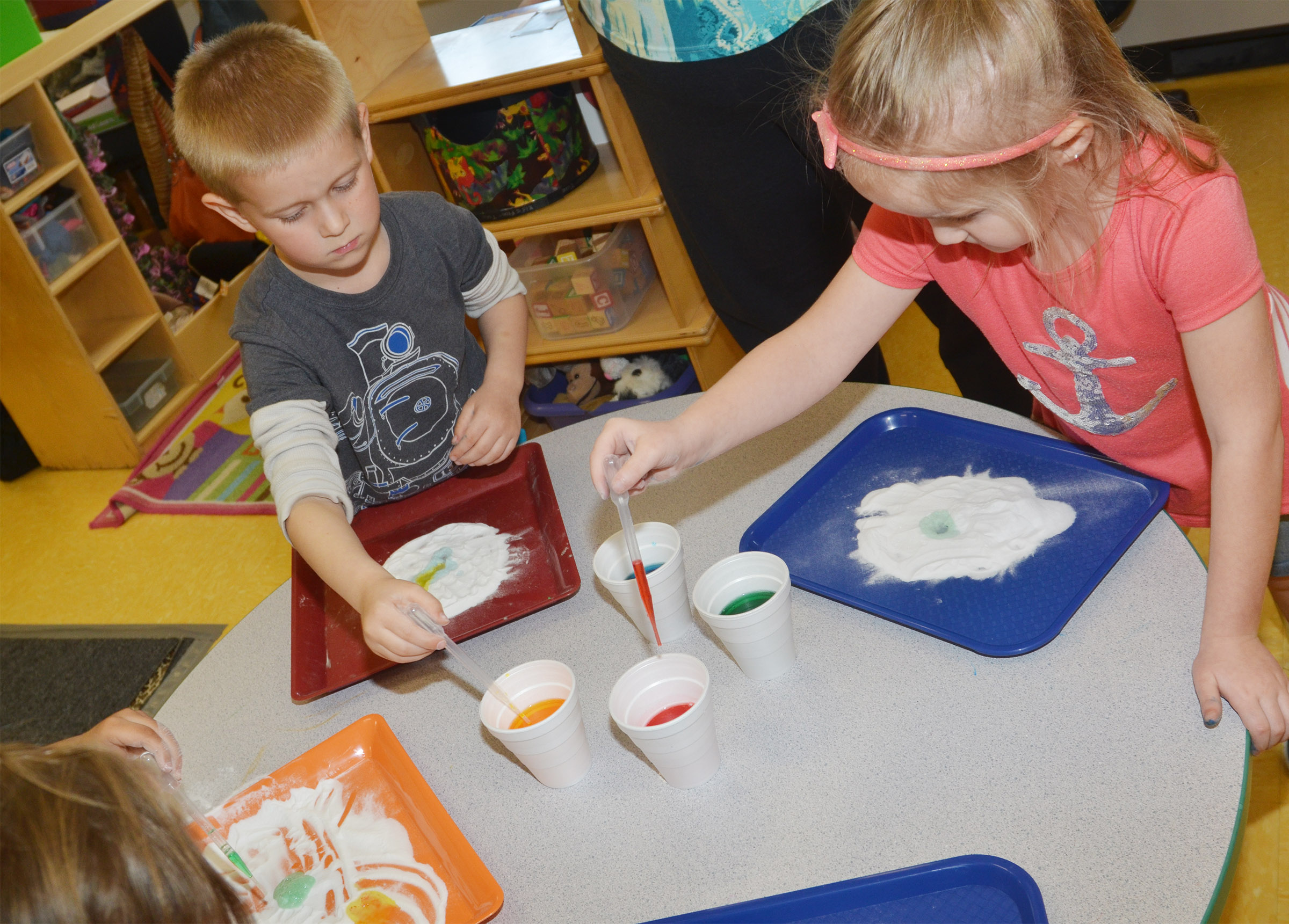 CES preschool students Jacob Parrish, at left, and Trinity Dye add colored vinegar to baking soda to see its reaction.
