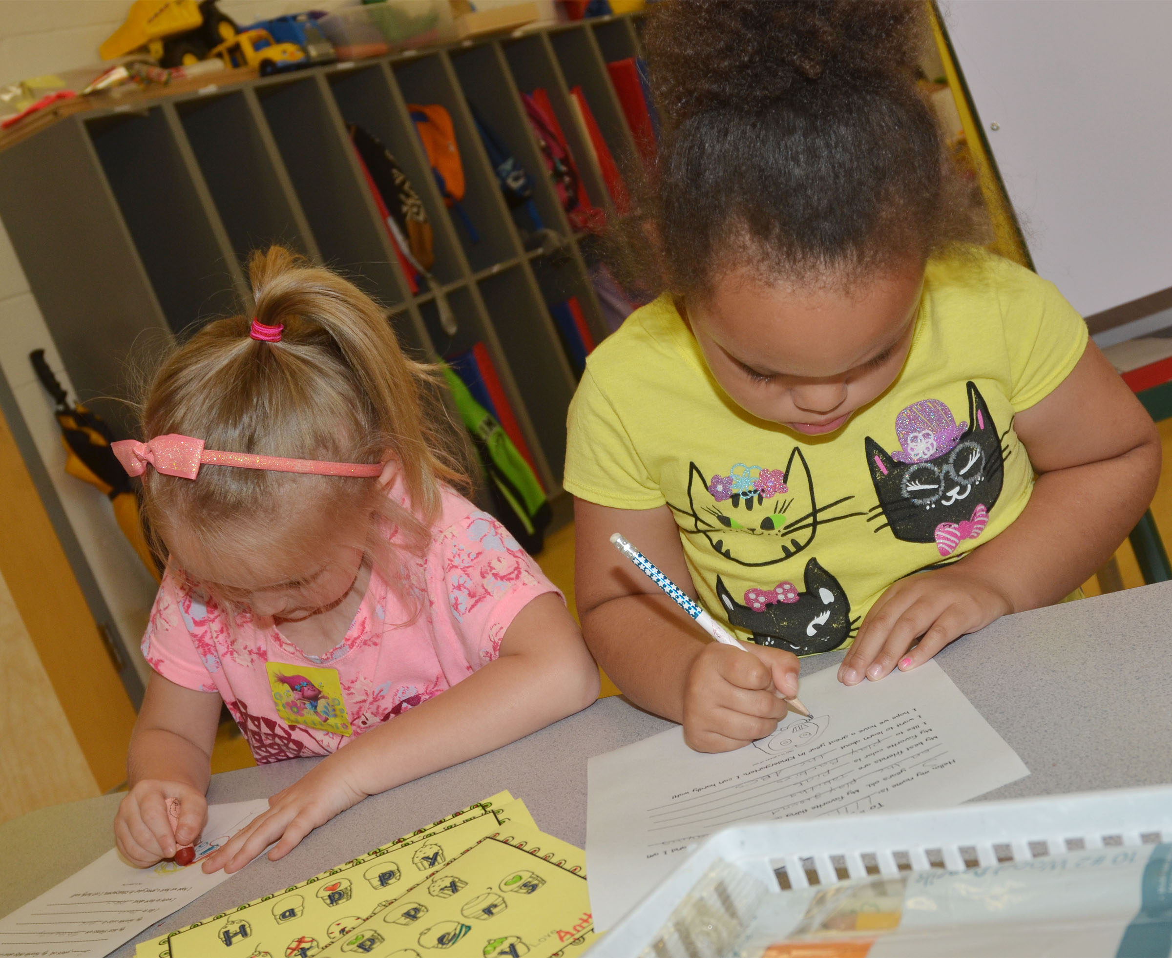 CES preschool students Trinity Dye, at left, and Lillian Merriweather draw their self-portraits for their letters to their kindergarten teachers.