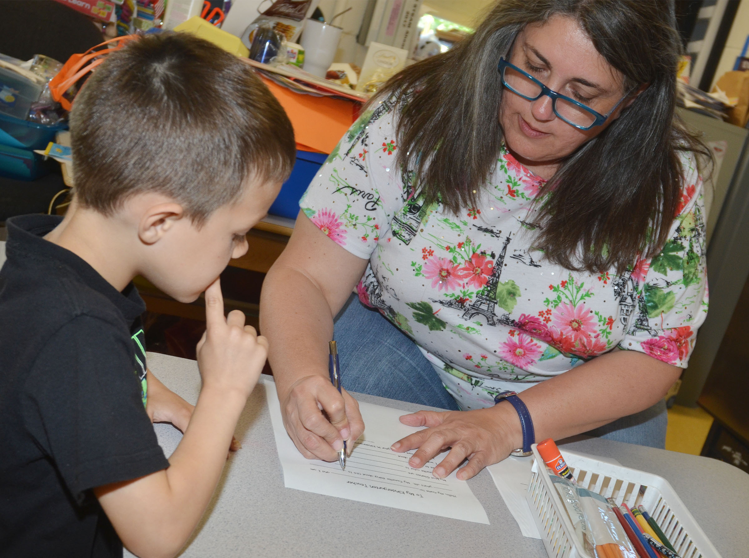 CES preschool student Levi Ritchie answers questions with teacher Sherry Cowherd as they write Ritchie's letter to his kindergarten teacher.