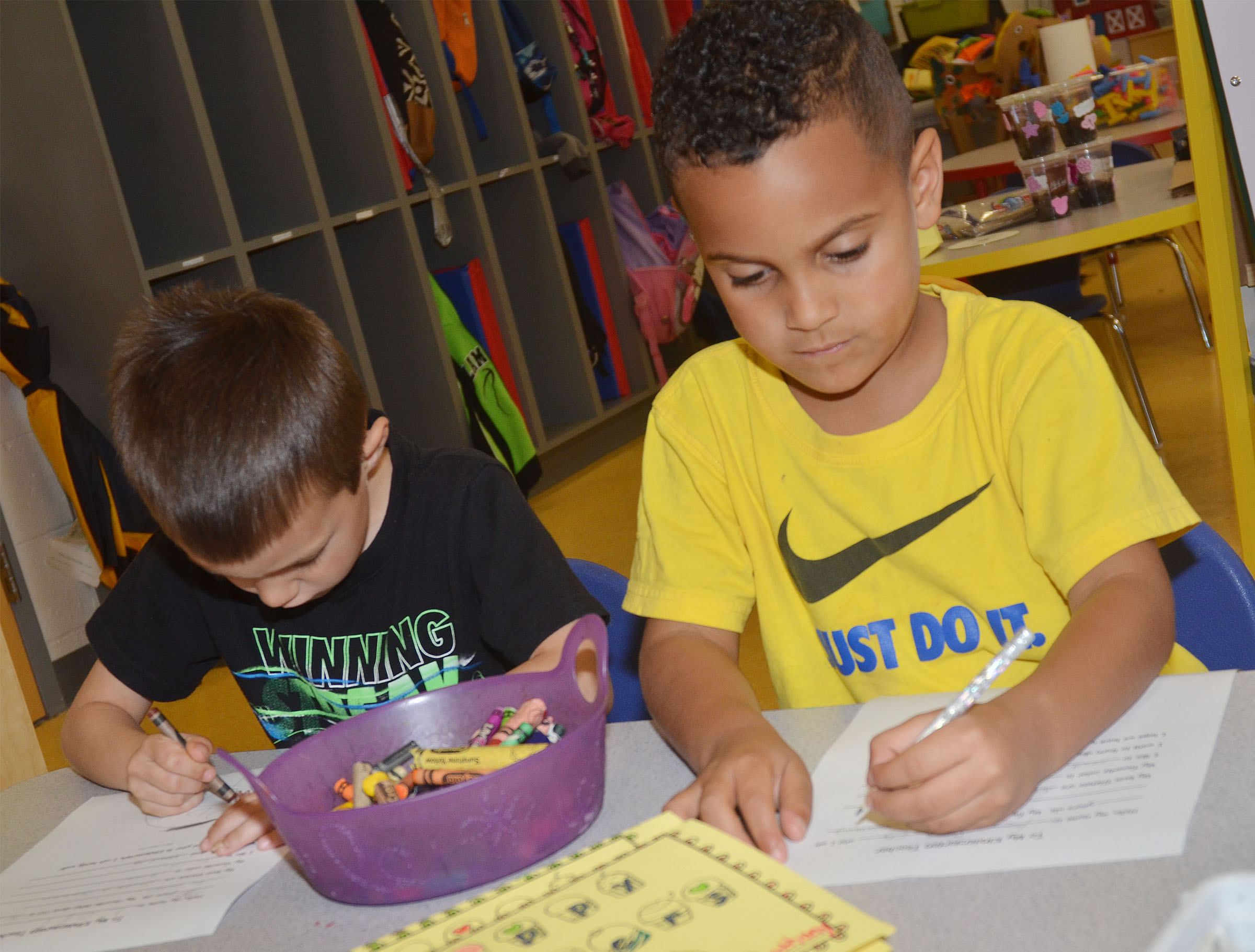 CES preschool students Levi Ritchie, at left, and Kingston Cowherd draw their self-portraits for their letters to their kindergarten teachers.