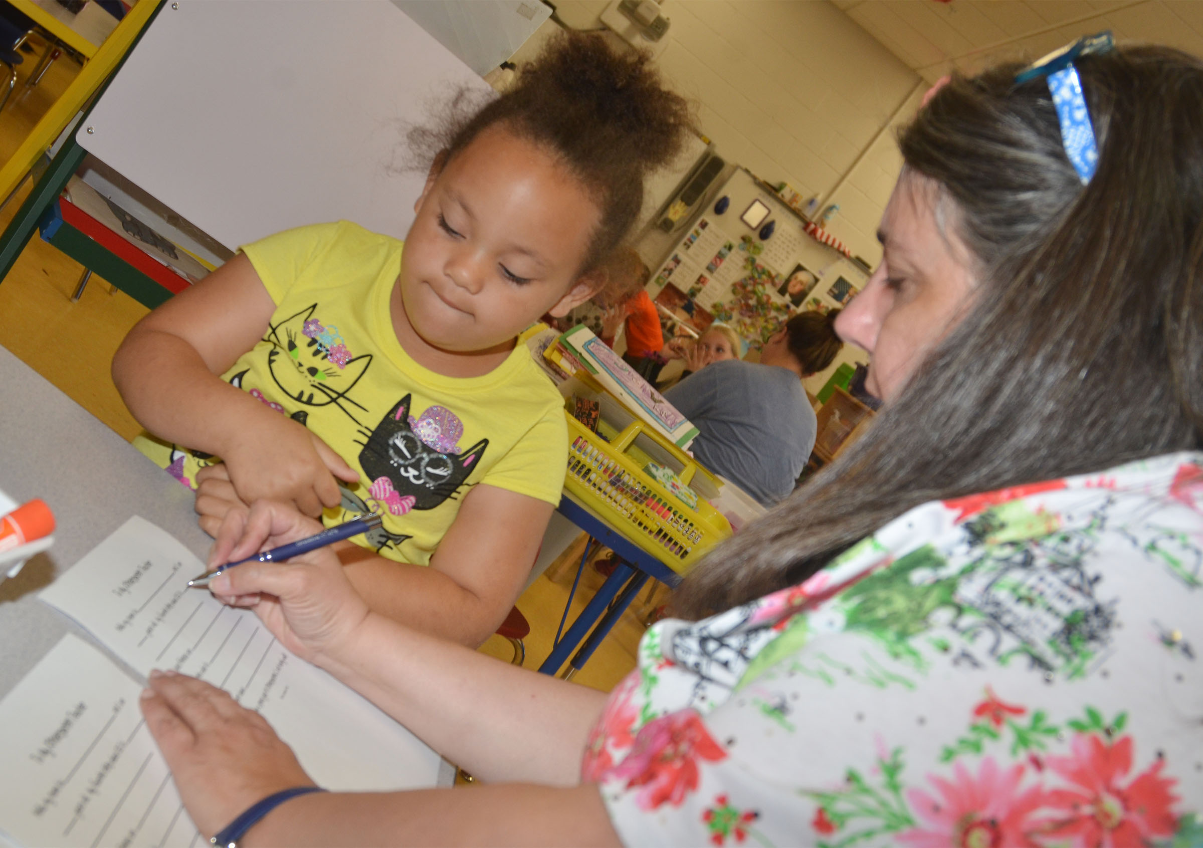 CES preschool student Lillian Merriweather answers questions with teacher Sherry Cowherd as they write Merriweather's letter to her kindergarten teacher.