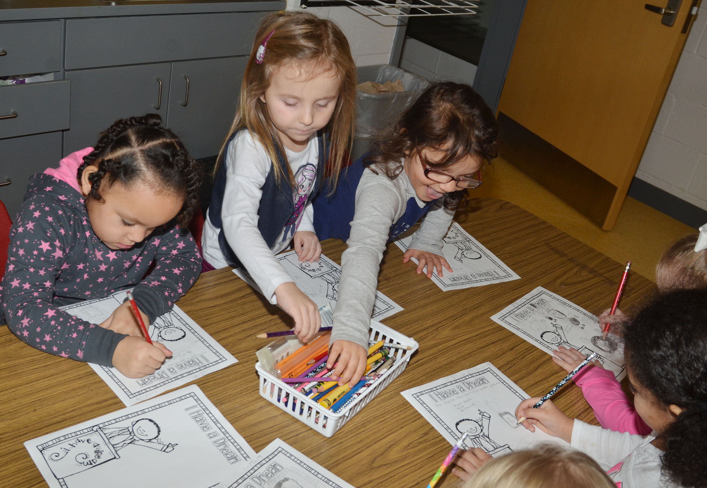 From left, CES preschool students Lillian Merriweather, Tabitha Leggett and Addisyn Taylor draw what they want to do when they grow up to change the world.