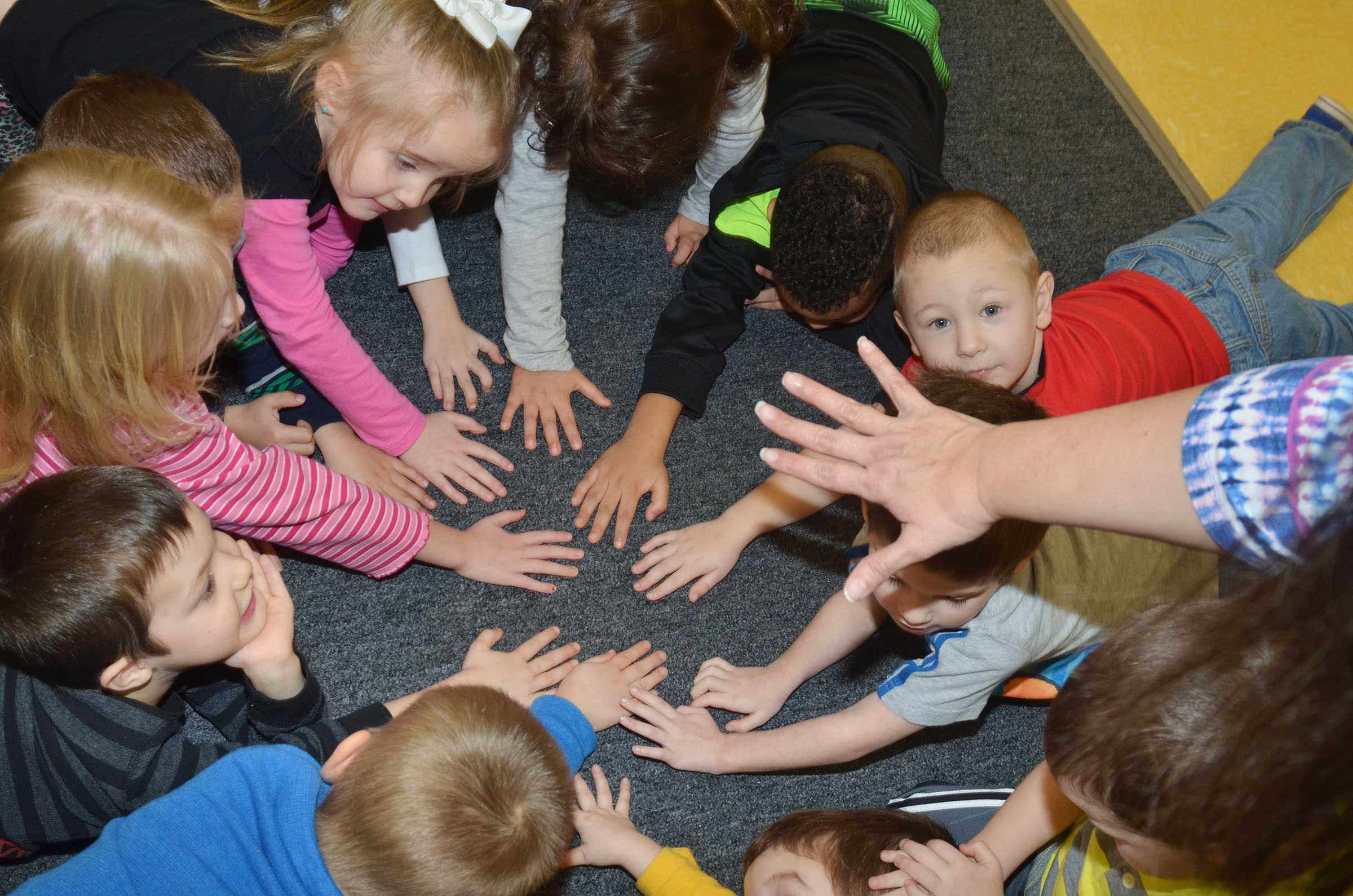 CES preschool teacher Sherry Cowherd places her hand in the circle of her students' hands, and asks them if any two people have the same skin color. Students agreed that they don't, but they are all equal and important.