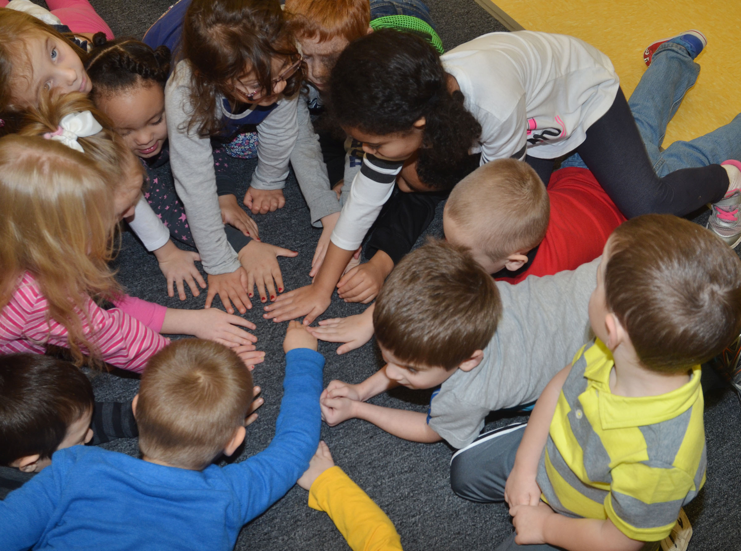 CES preschool students place their hands in a circle to see if any two people have the same skin color. Students agreed that they don't, but they are all equal and important.