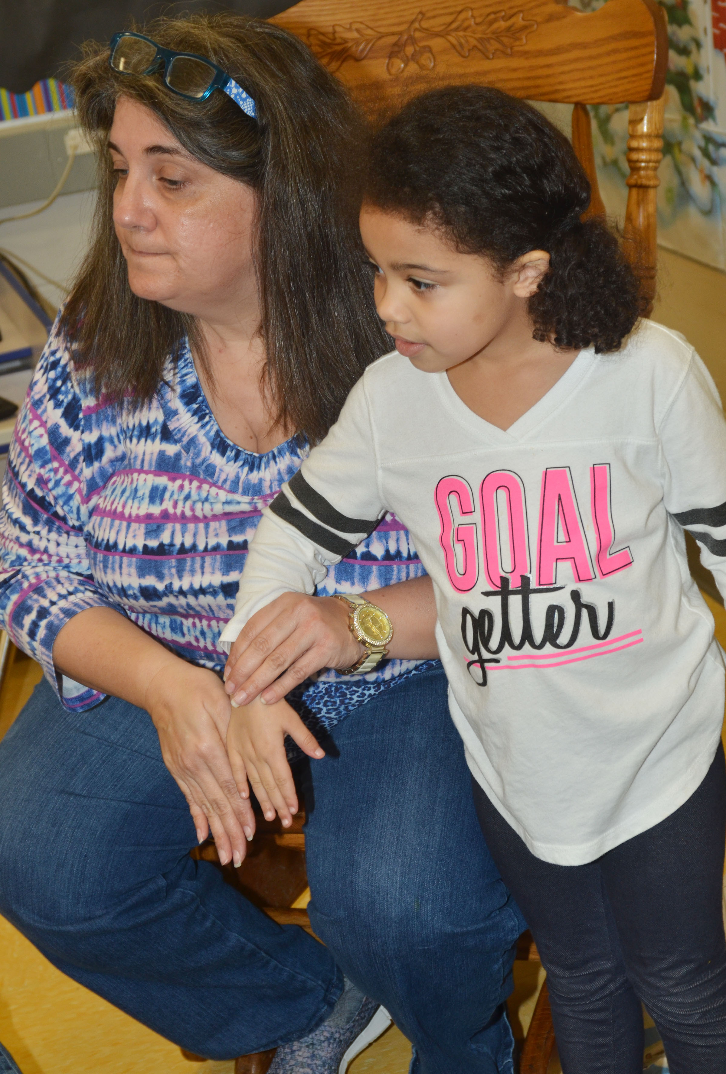 CES preschool teacher Sherry Cowherd places her hand beside Rylee Karr's to see if they are the same.