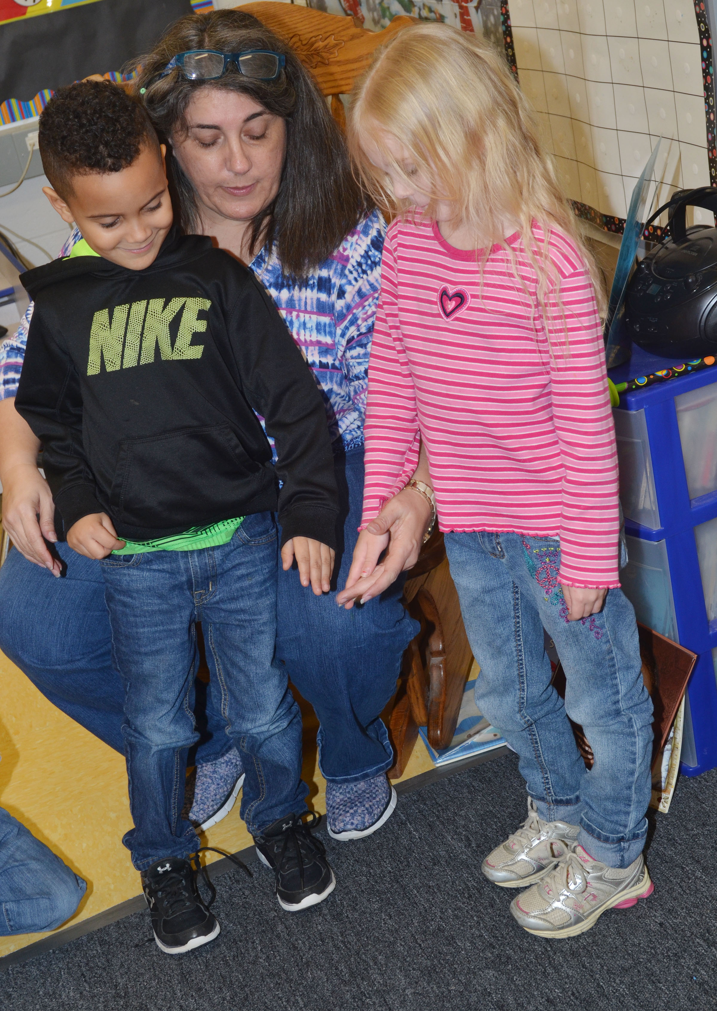 CES preschool teacher Sherry Cowherd places Kingston Cowherd's hands beside Alinna Bray's to see if they are the same color.