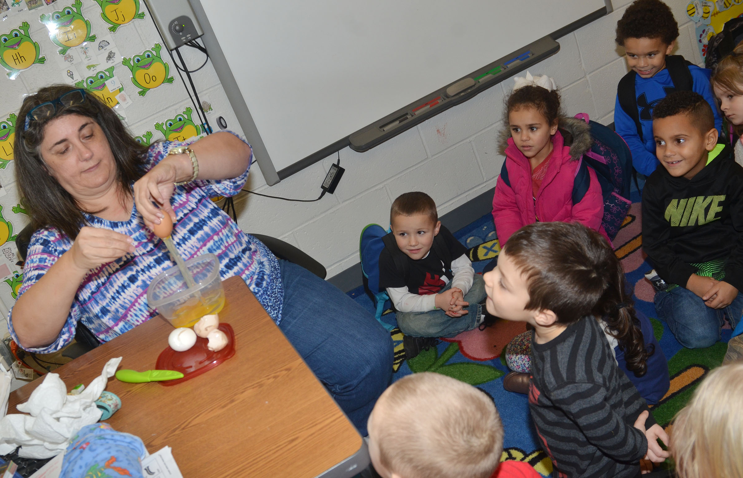 CES preschool teacher Sherry Cowherd shows students that tan, brown and white eggs are the same on the inside even though they are different on the outside.