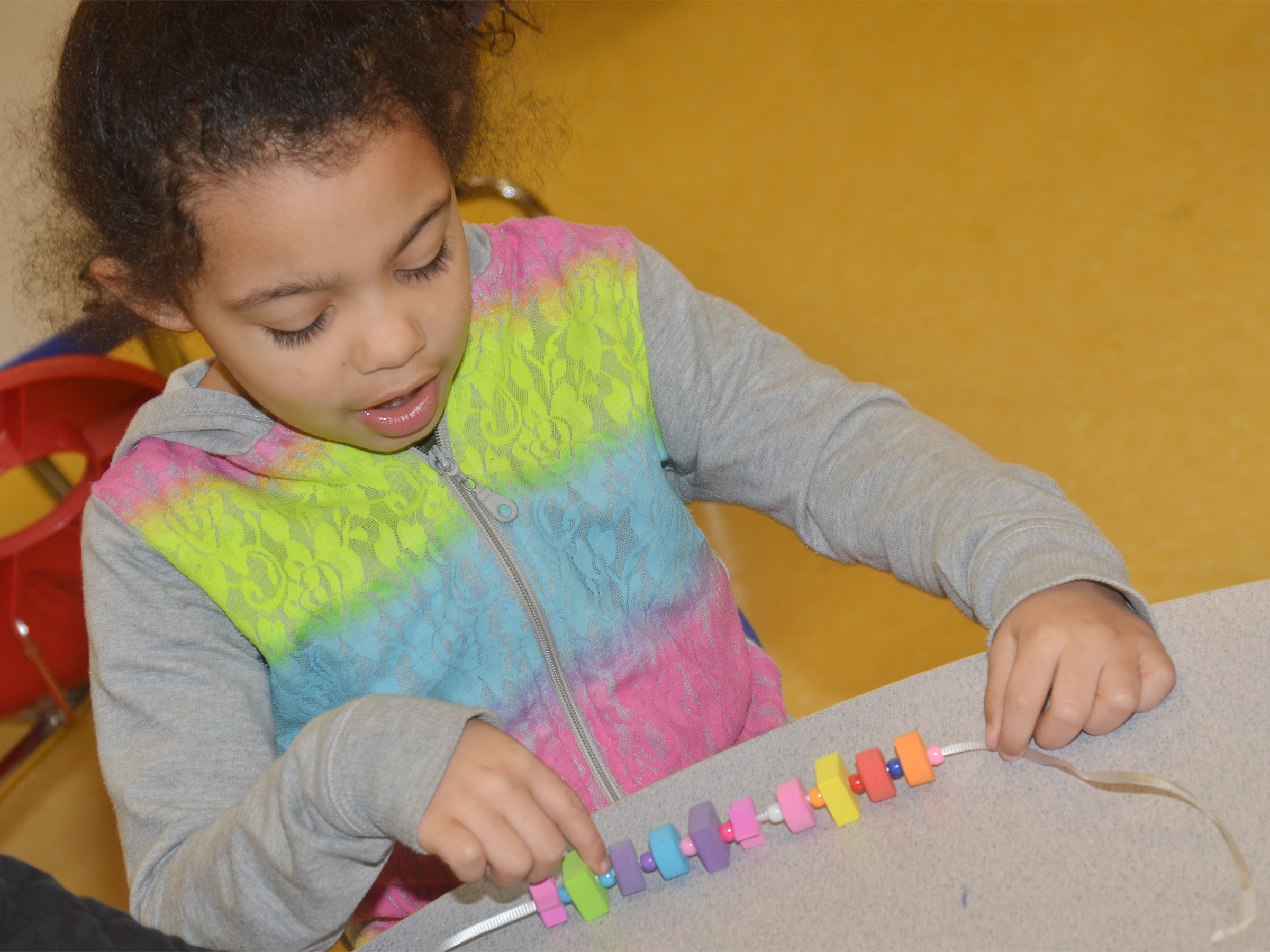 CES preschool student Rylee Karr makes a necklace with a color and shape pattern.