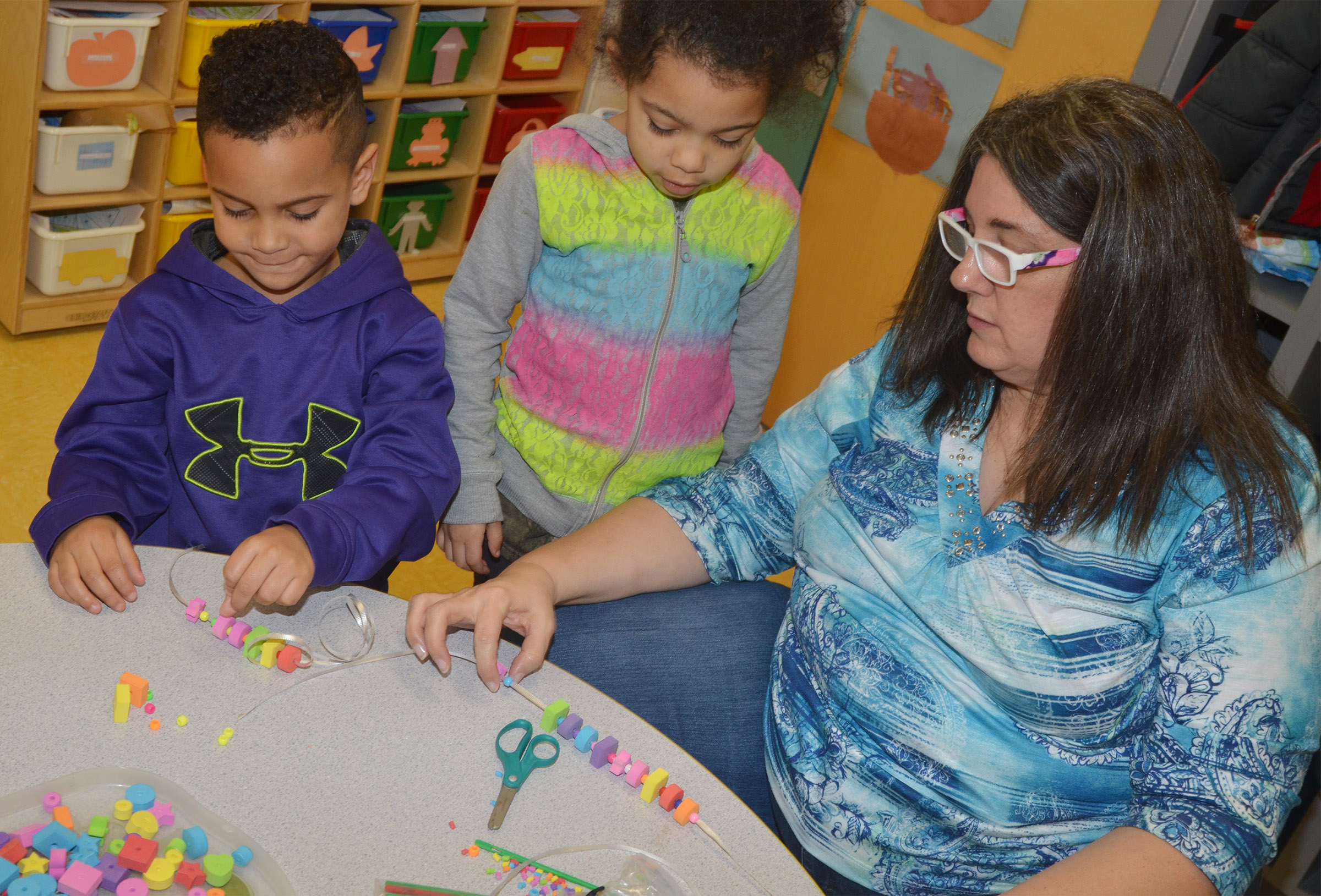 CES preschool teacher Sherry Cowherd helps students Kingston Cowherd, at left, and Rylee Karr make necklaces with a color and shape pattern.