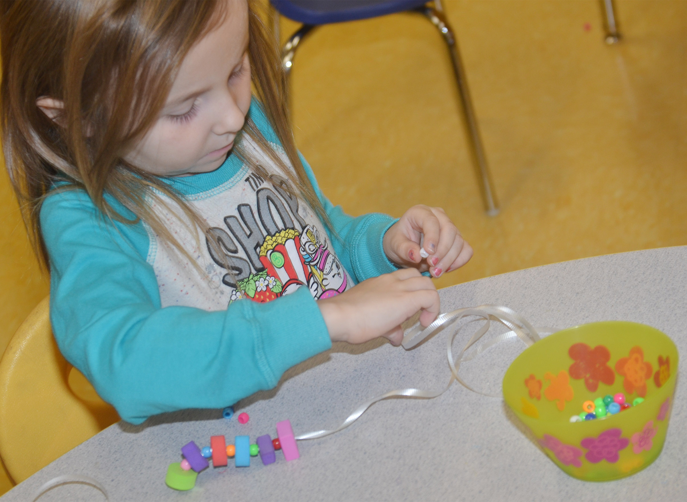 CES preschool student Tabitha Leggett makes a necklace with a color and shape pattern.