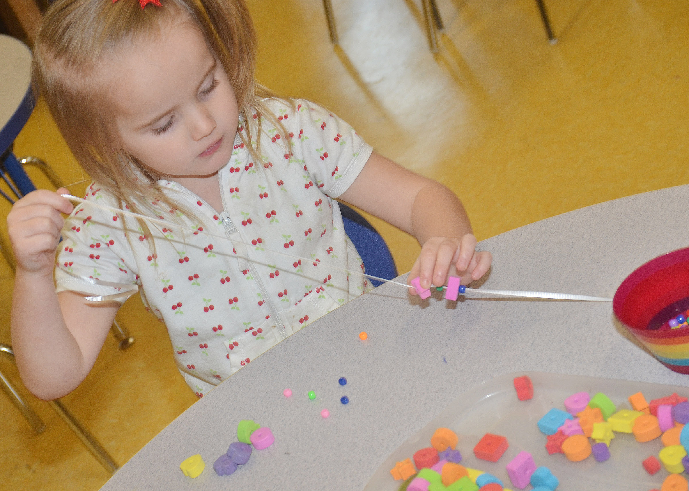 CES preschool student Trinity Dye makes a necklace with a color and shape pattern.