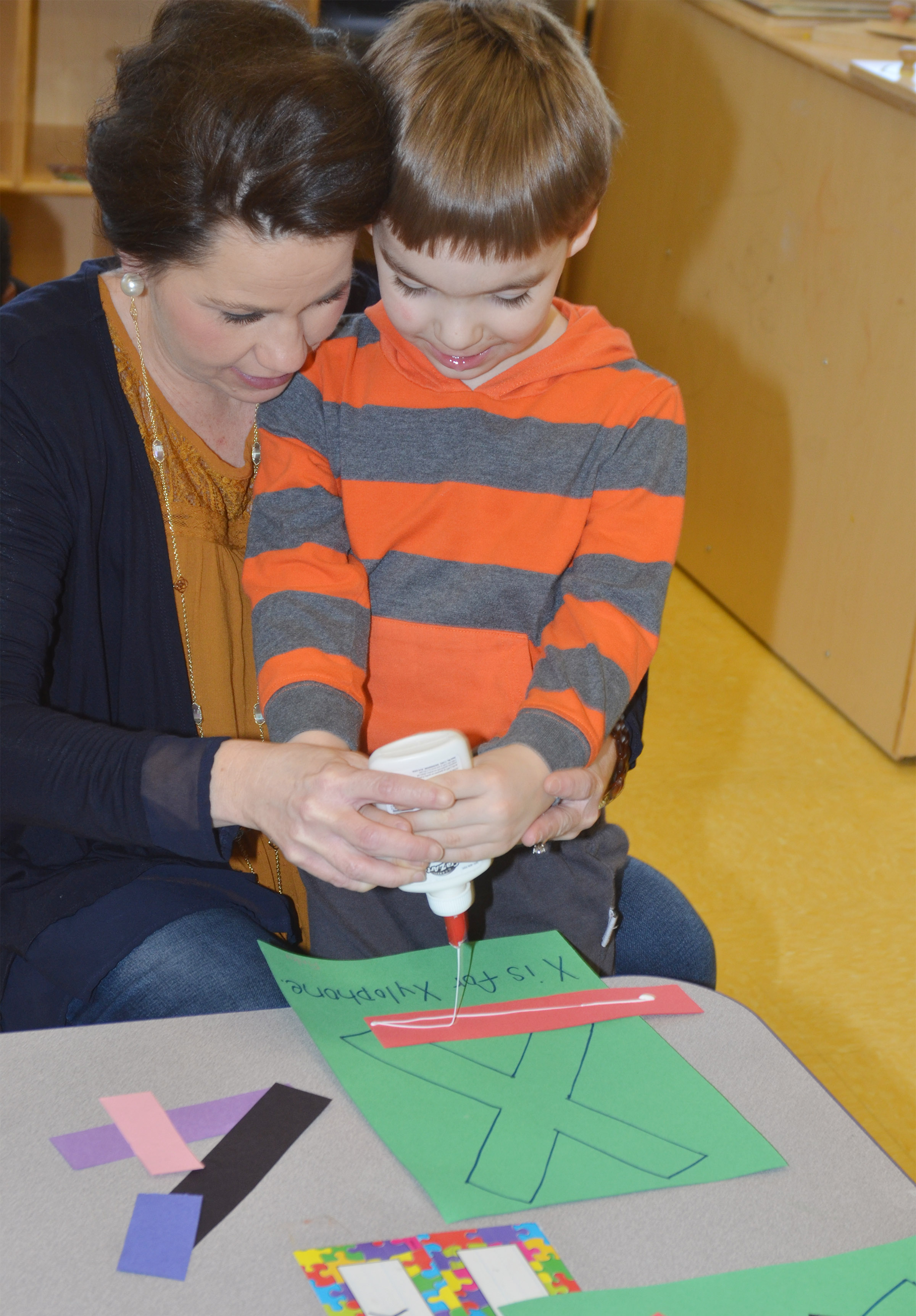 CES preschool assistant Beth Sandidge helps Finley Williams make his xylophone as he learns all about the letter X.