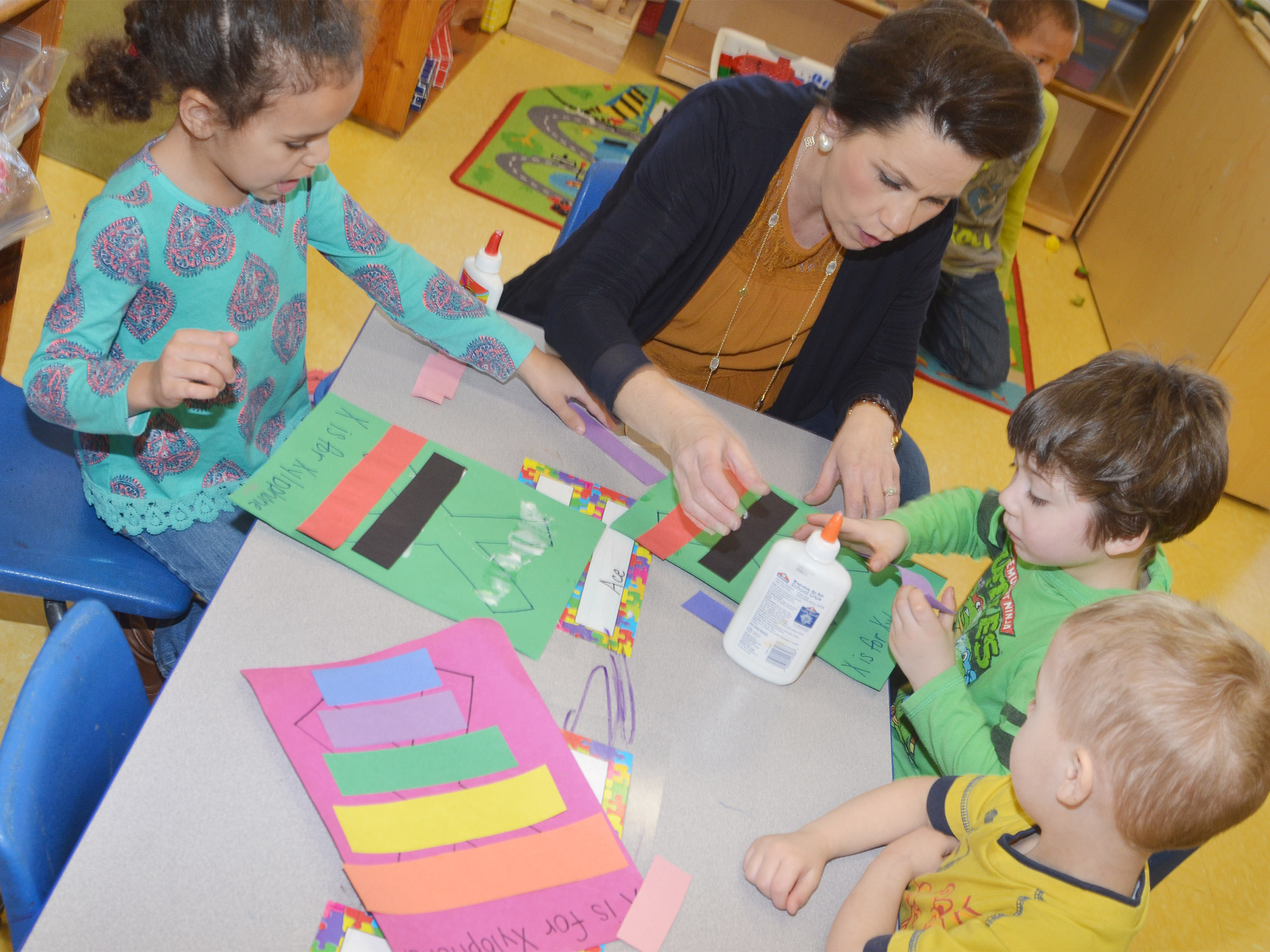 CES preschool assistant Beth Sandidge helps, from left, Adelyn Litsey, Josiah Dean and Chase Russell make their xylophones as they study the letter X.