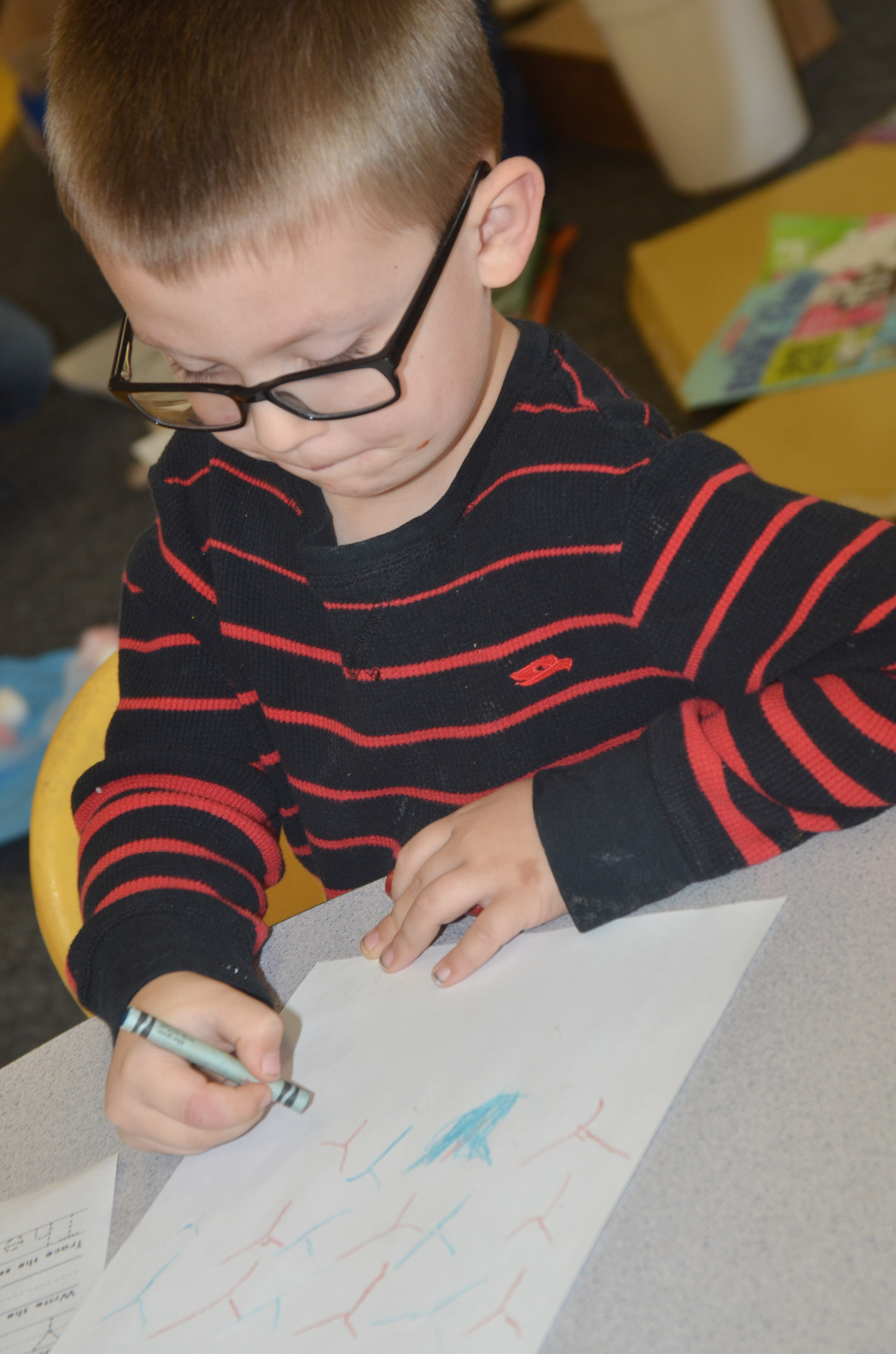 CES preschool student Reece Williams writes the letter Y.