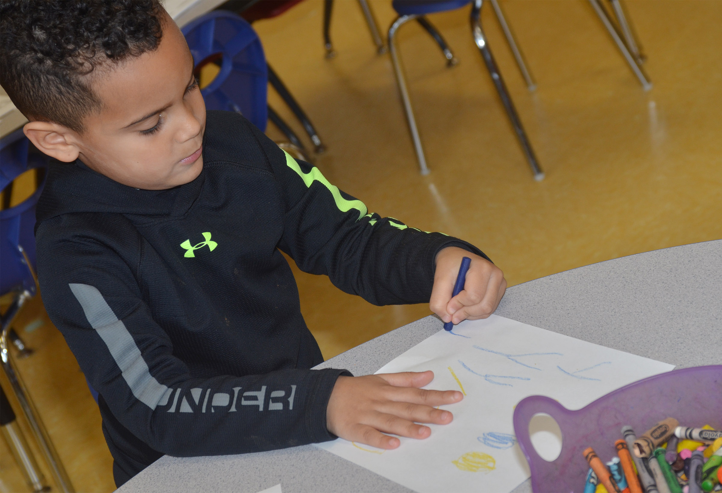 CES preschool student Kingston Cowherd practices writing the letter Y.