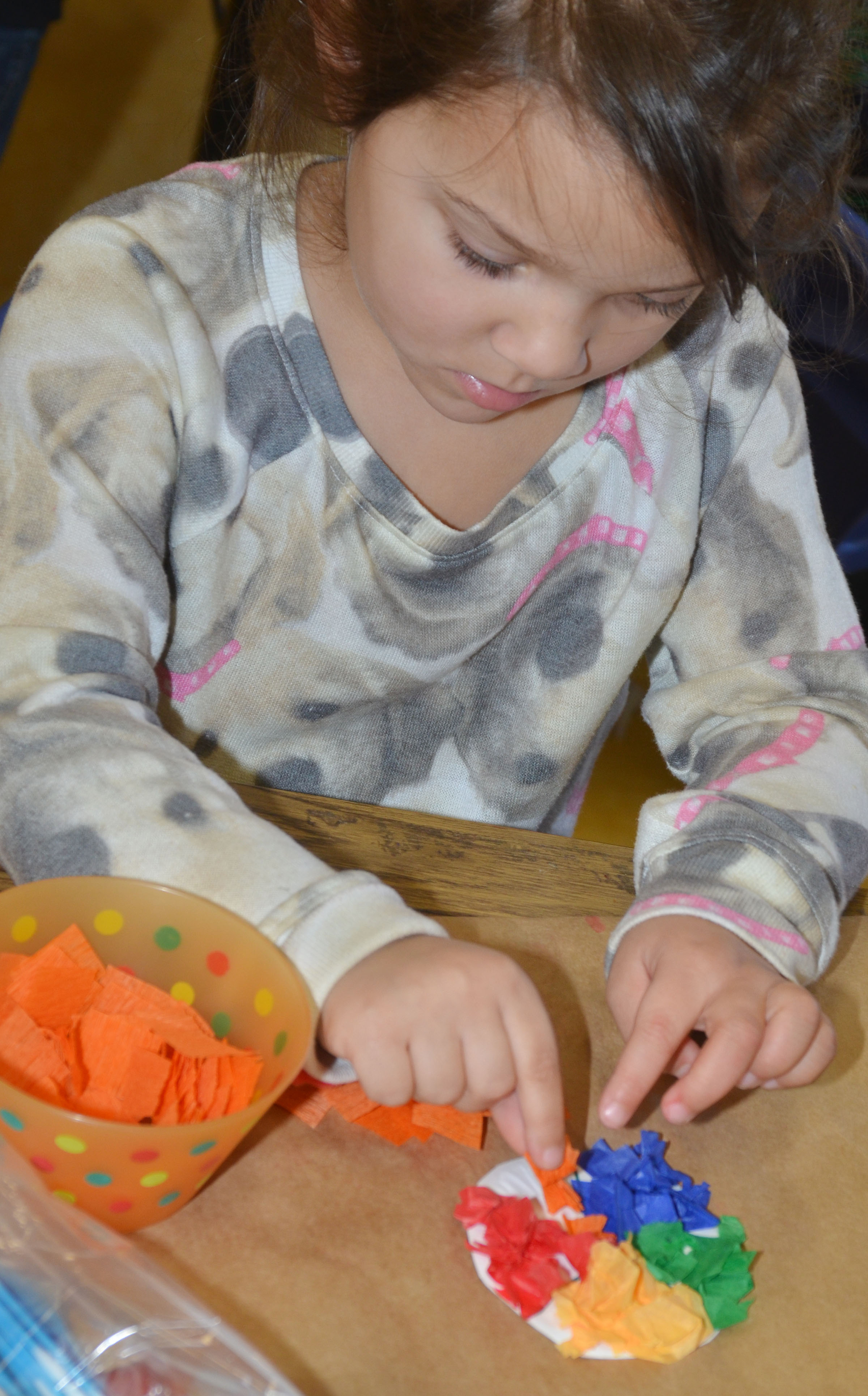 CES preschool student Addisyn Taylor adds orange paper to her lollipop.