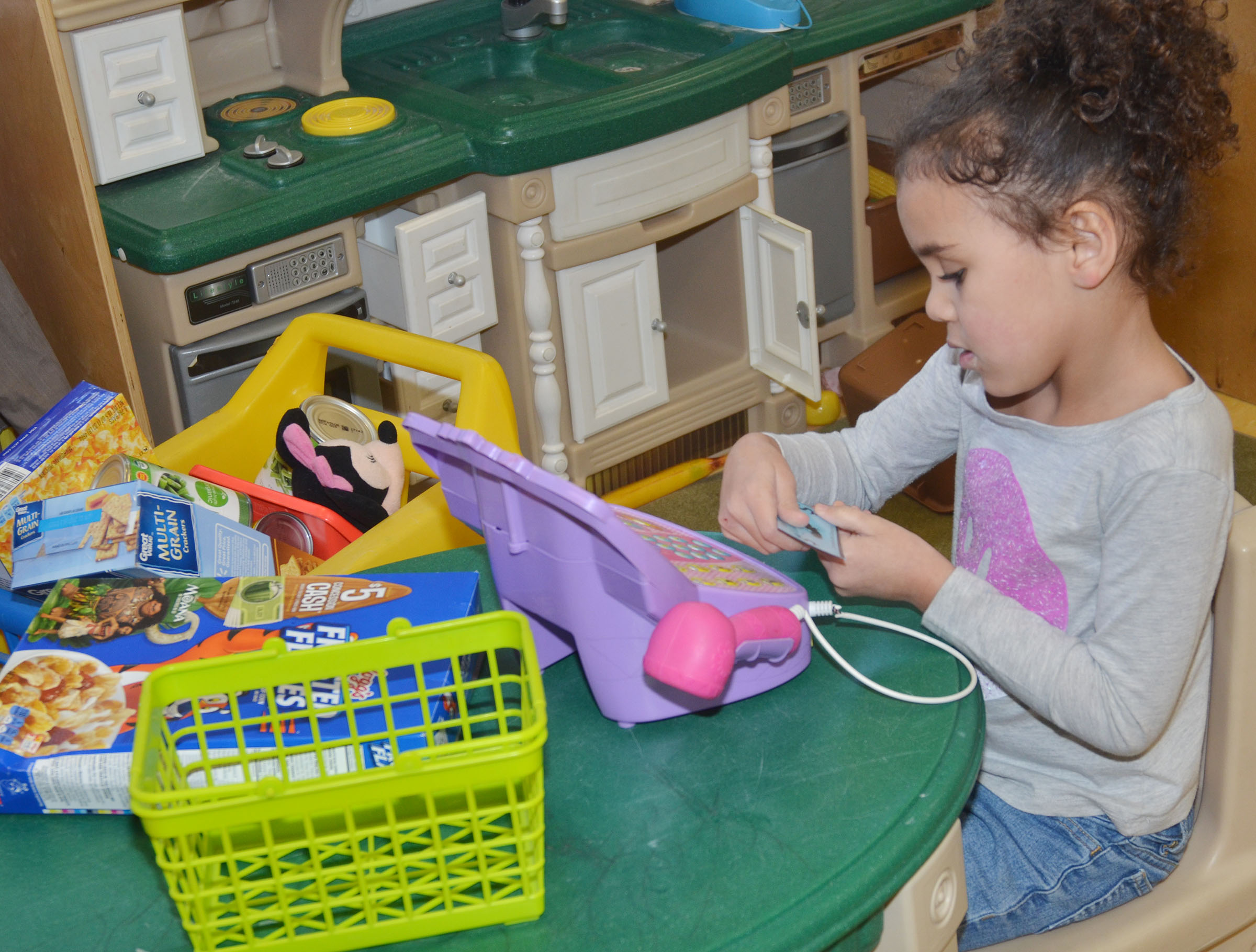 "CES preschool student Adelyn Litsey counts her ""money."""